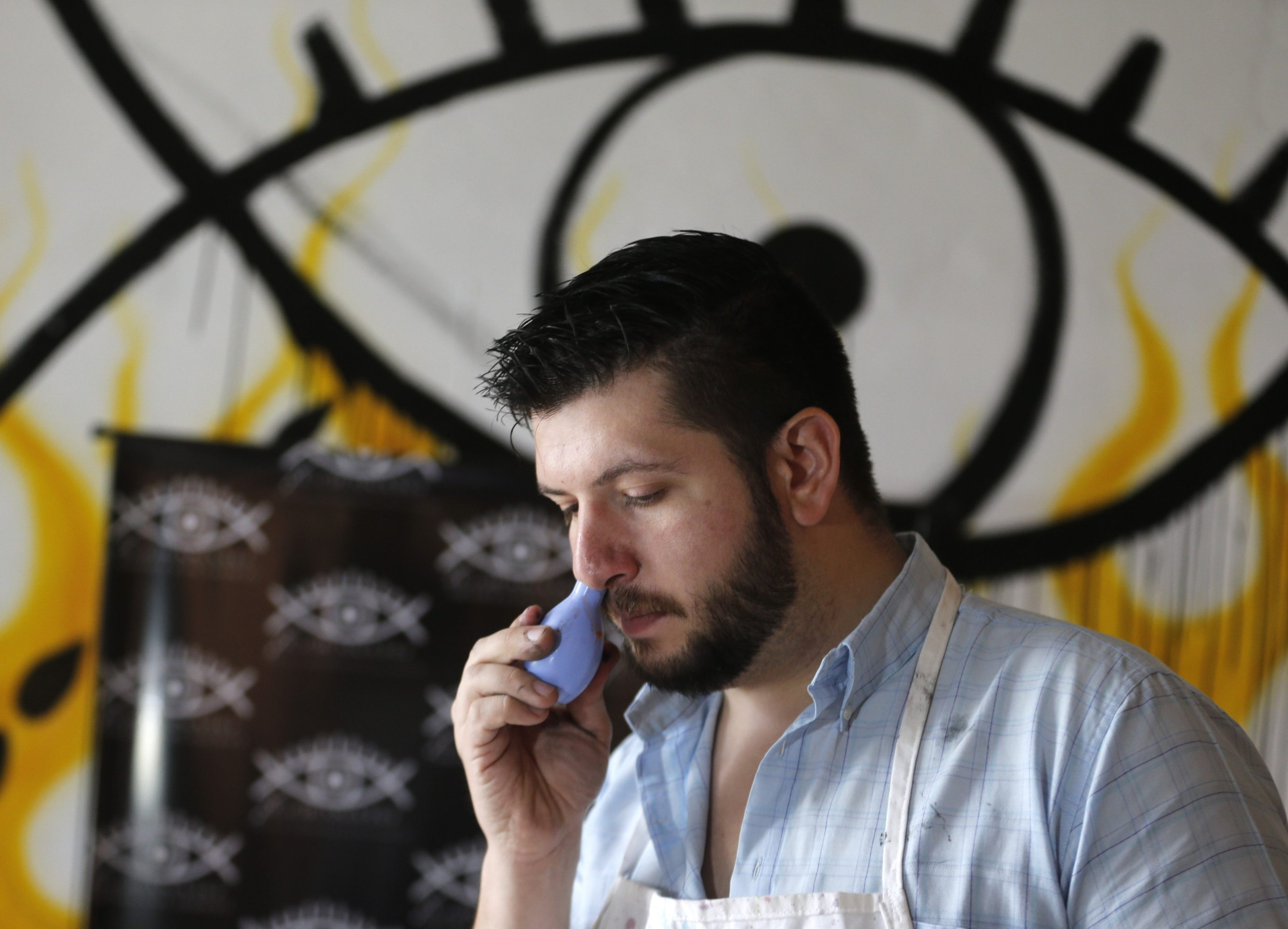 Artist Leandro Granato inhales paint as he prepares to paint at his studio in Alejandro Korn town in greater Buenos Aires, Argentina, Oct. 10, 2013. (REUTERS Photo)