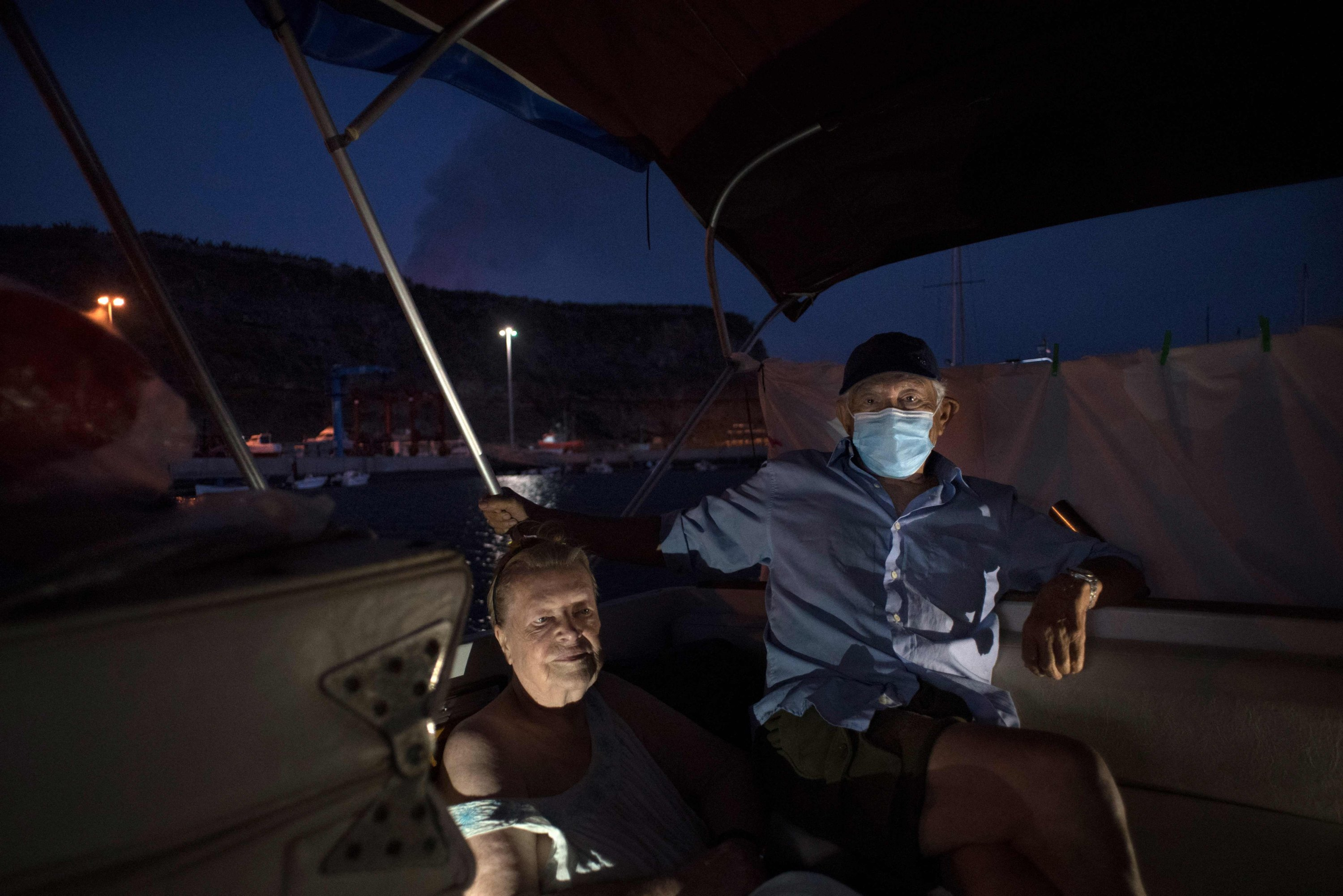 Margaretha and Luis, 80 and 90 years old, wait on their boat where they have settled after fleeing their home after the eruption of the Cumbre Vieja volcano, in the port of Tazacorte, on La Palma, Spain, Oct. 3, 2021. (AFP Photo)