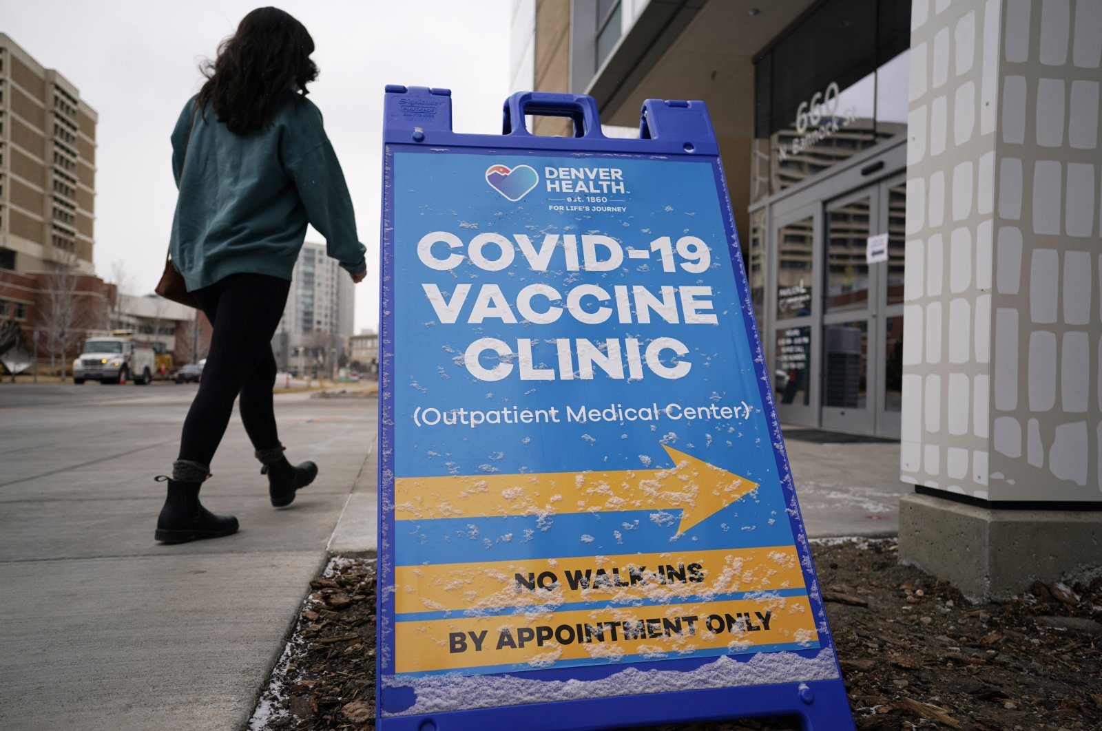 A woman heads in for a COVID-19 vaccination during a mass vaccination of 1,000 employees of Denver Public Schools including teachers, administrators, custodial workers and bus drivers at Denver Health, in Denver, Colorado, U.S., Feb. 13, 2021. (AP File Photo)