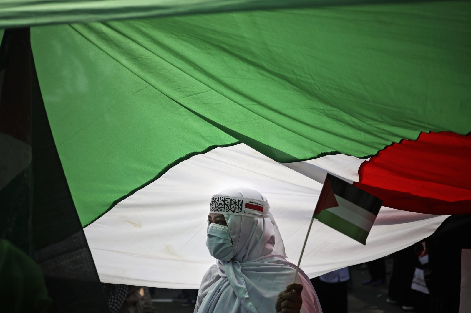 A protester stands under a large Palestinian flag during an anti-Israel rally outside the U.S. Embassy in Jakarta, Indonesia, May 18, 2021. (AP Photo)