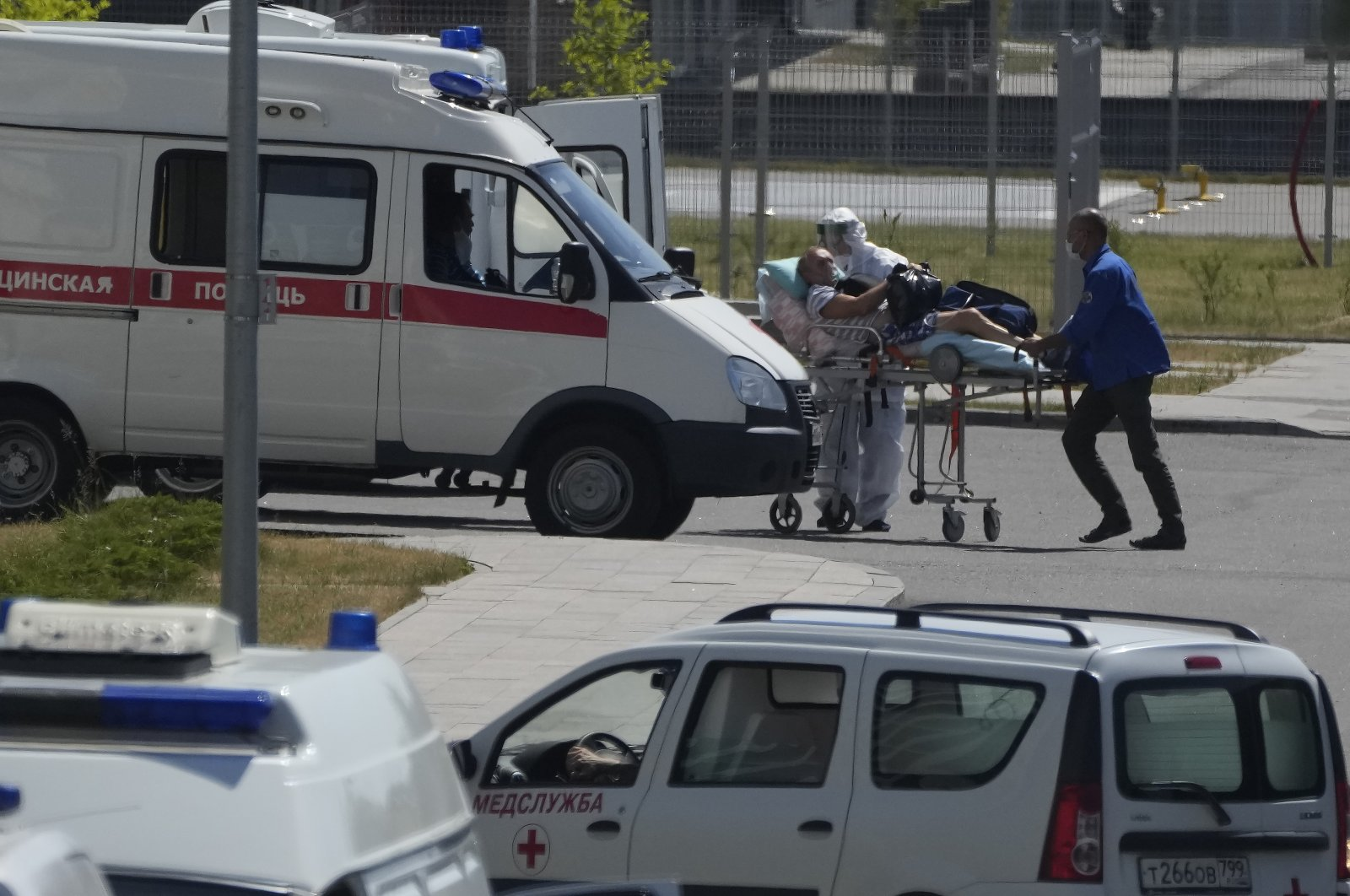 A medical worker wearing protective gear escorts a man, suspected of having COVID-19, at a hospital in Kommunarka, outside Moscow, Russia, July 12, 2021. (AP Photo)