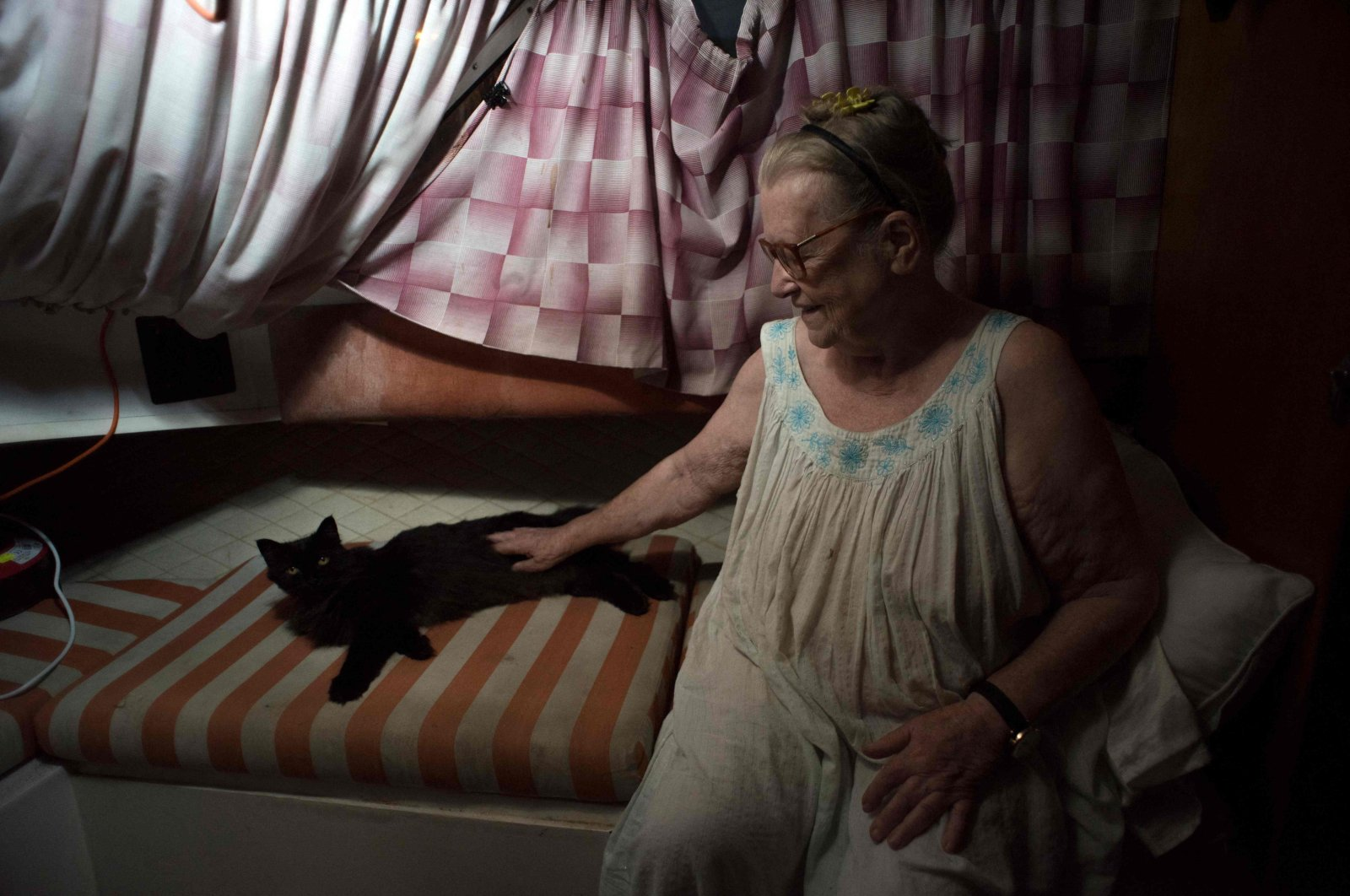 Margaretha, 80, sits next to her cat on the boat where she and her husband have settled after fleeing their home after the eruption of the Cumbre Vieja volcano, in the port of Tazacorte, on La Palma, Spain, Oct. 3, 2021. (AFP Photo)