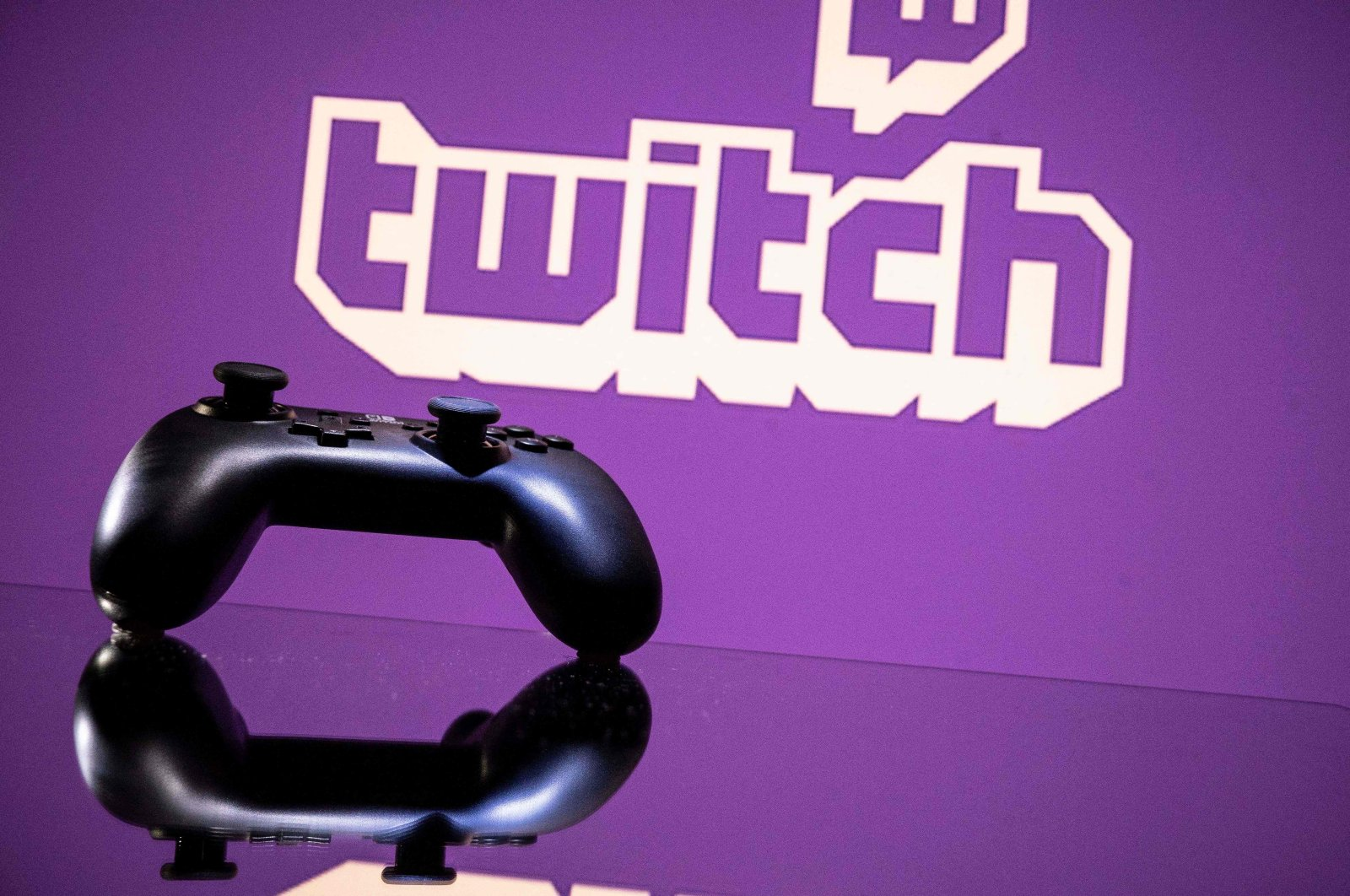 A console controller is pictured in front of a screen displaying the logo of Twitch in Toulouse, southwestern France, June 15, 2021 (AFP Photo)