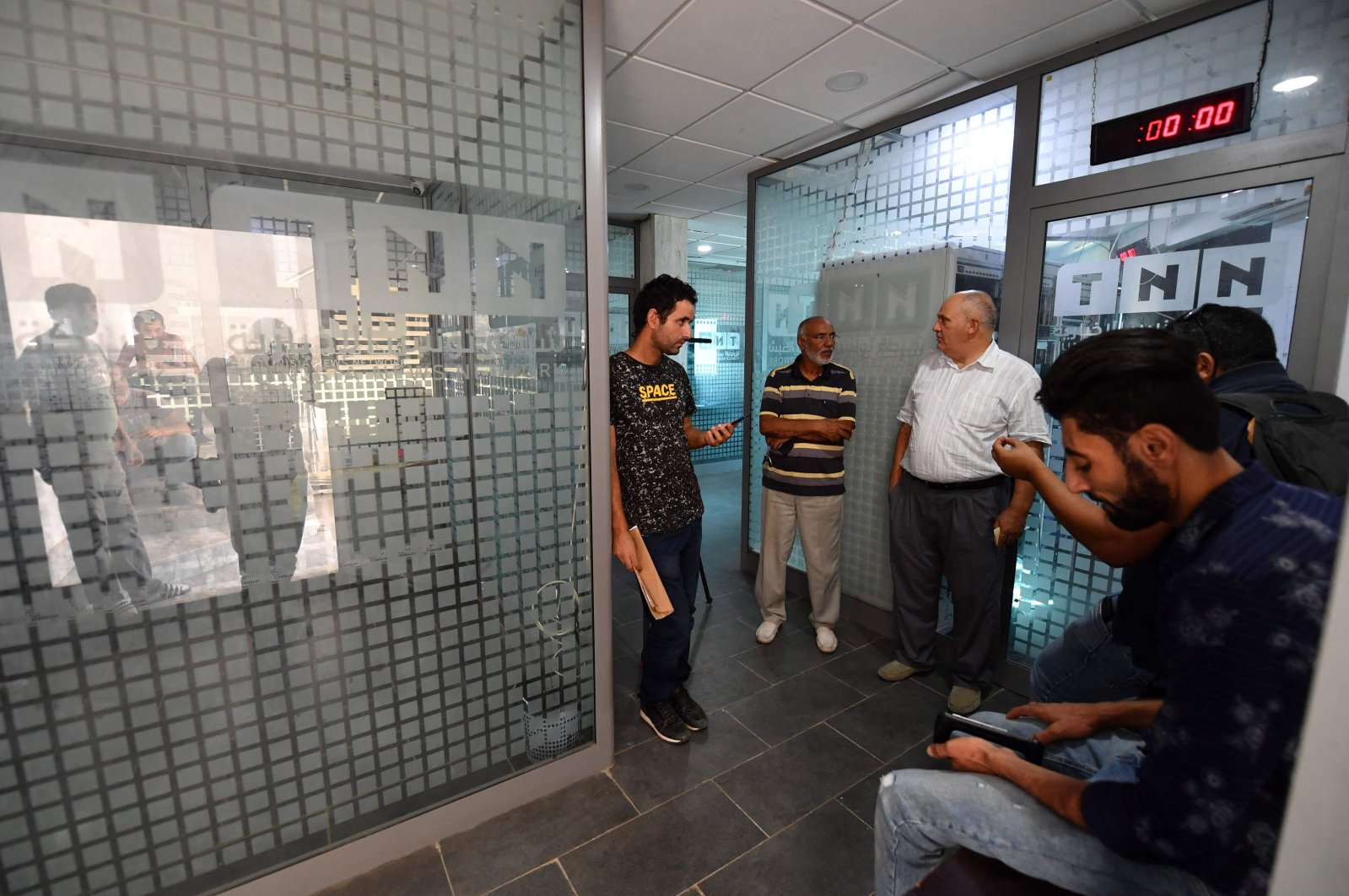 Employees gather inside the building housing the Zitouna TV channel gather on October 6, 2021, after Tunisian authorities seized broadcasting equipment, in the district of Mghira of greater Tunis, the country's capital. (AFP Photo)