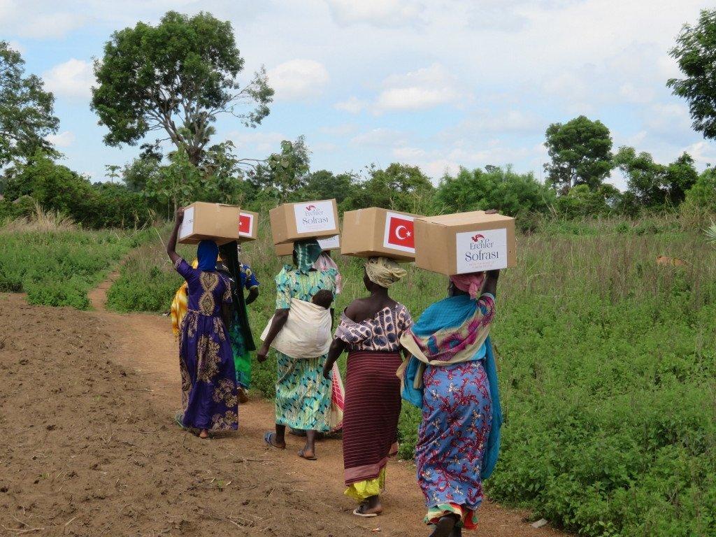 Ugandan women carry aid packages donated by Turkey's TIKA, in Yumbe, Uganda, May 7, 2021. (Courtesy of TIKA)