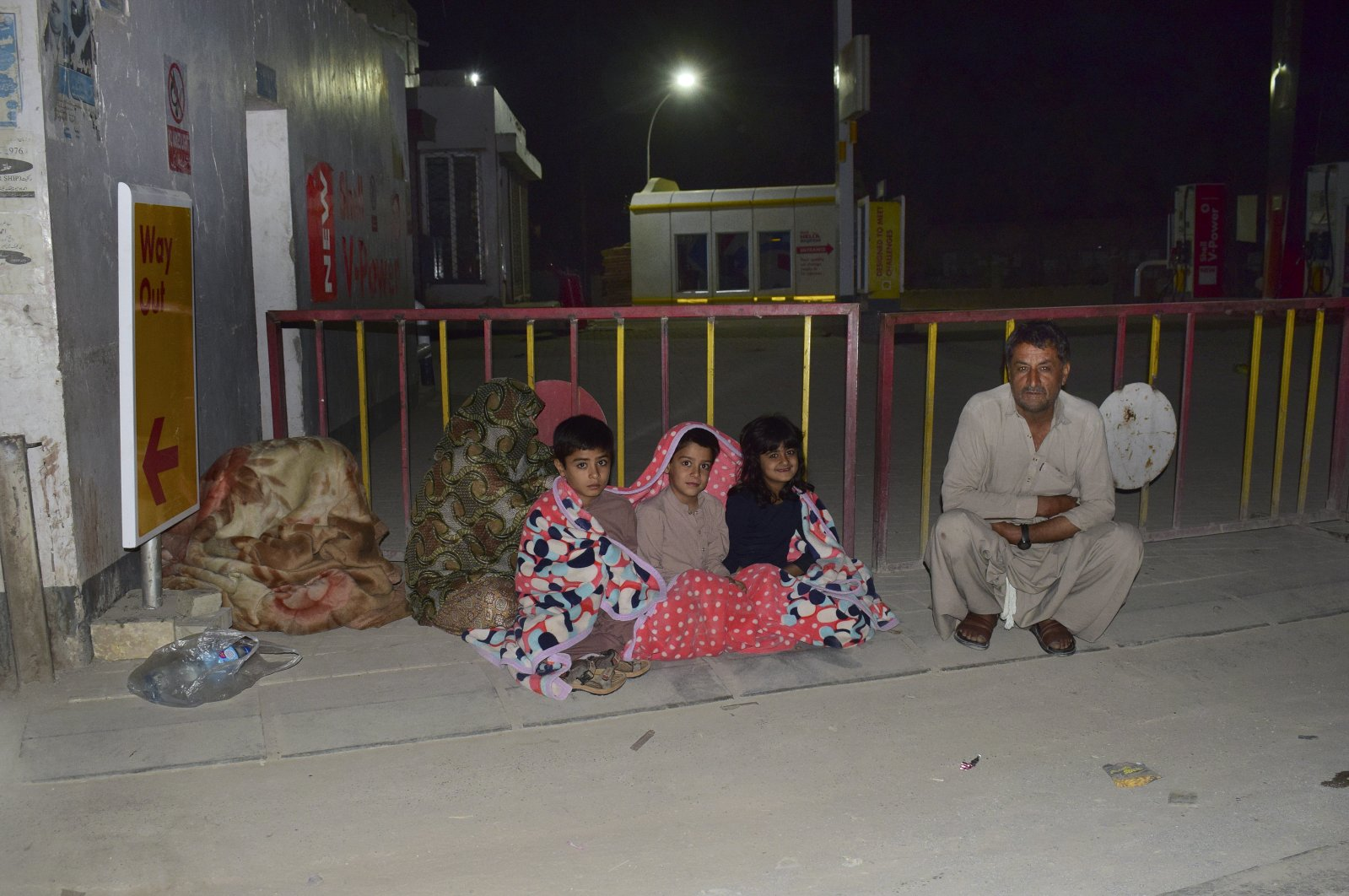 A family gather outside their house following a severe earthquake that hit the area, in Quetta, Pakistan, Thursday, Pakistan. (AP Photo)