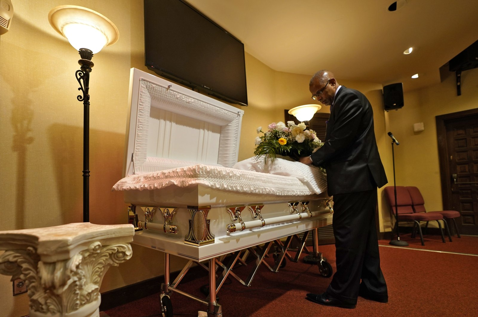 A funeral director arranges flowers on a casket before a service in Tampa, Florida, U.S., Sept. 2, 2021. (AP Photo)