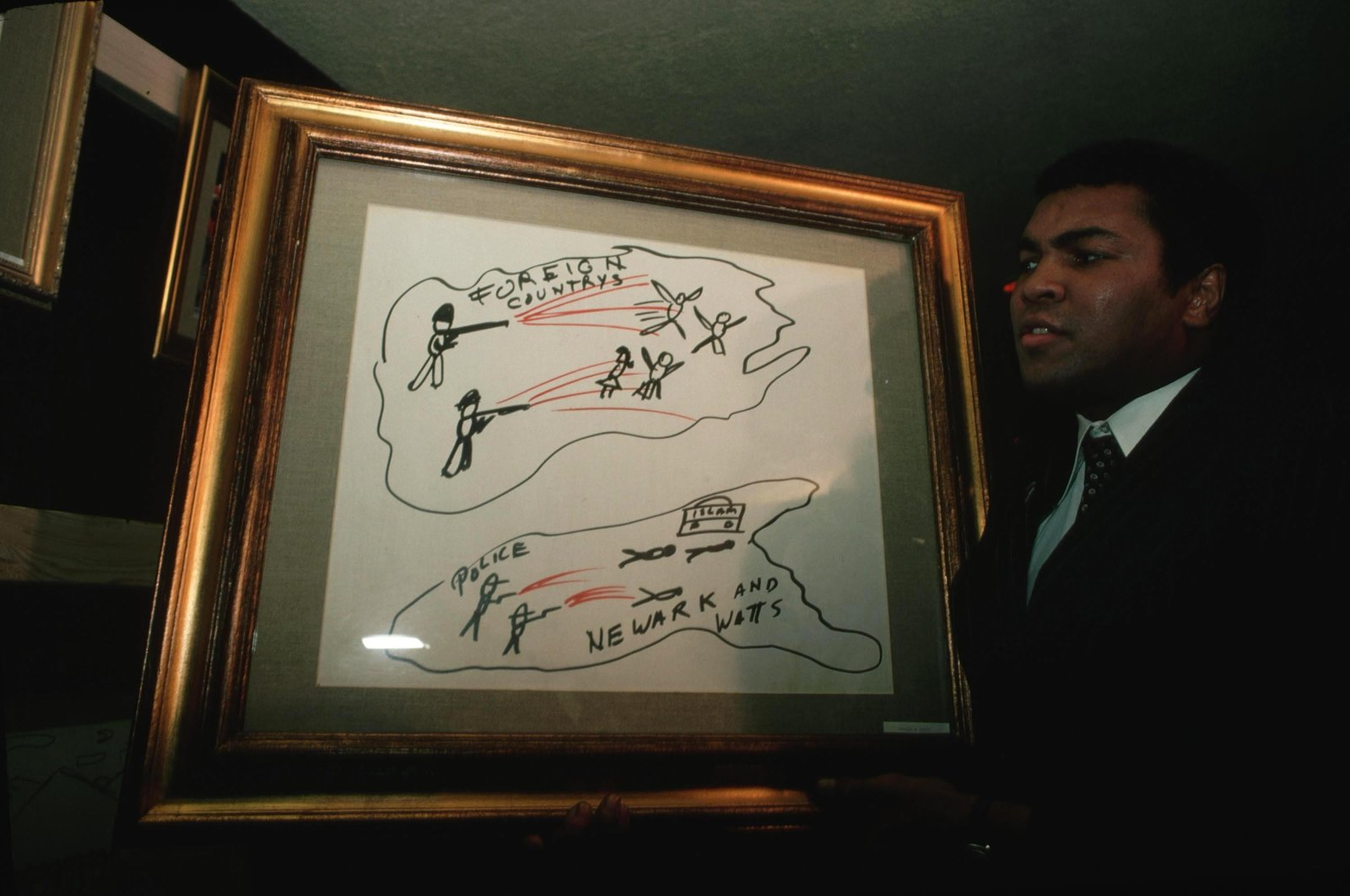 Muhammad Ali holding his artwork at an exhibit.  (Getty Images)