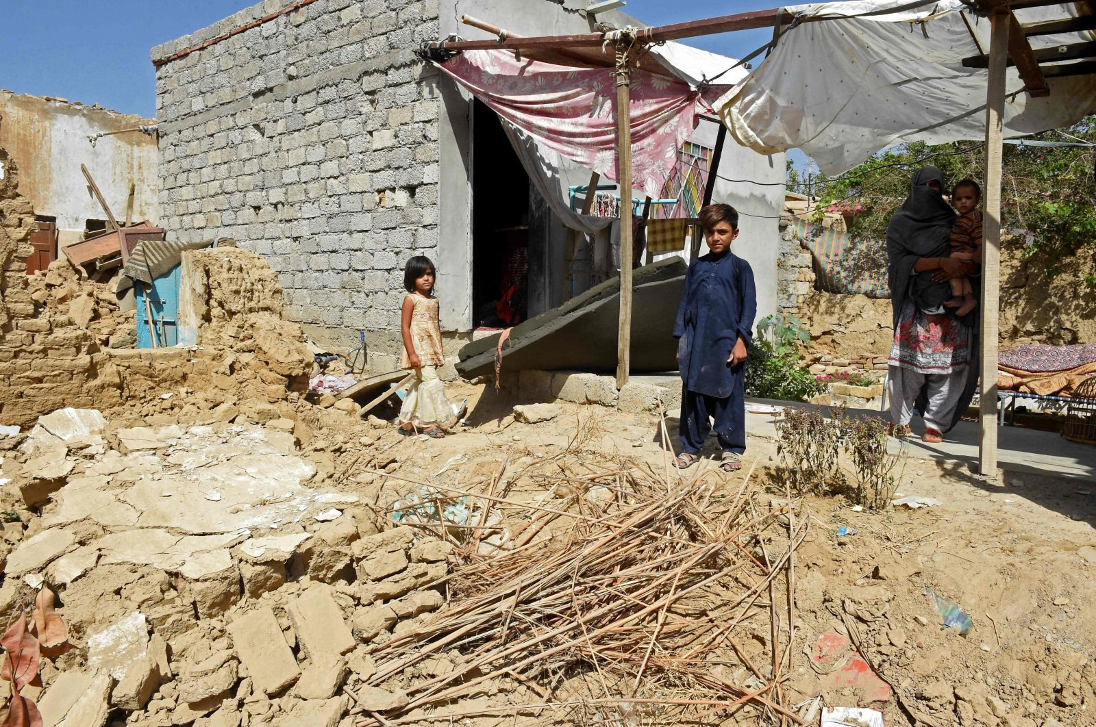 A woman and her children stand beside their collapsed mudbrick house following an earthquake in the remote mountainous district of Harnai early on Oct. 7, 2021, southwestern Pakistan. (AFP Photo)