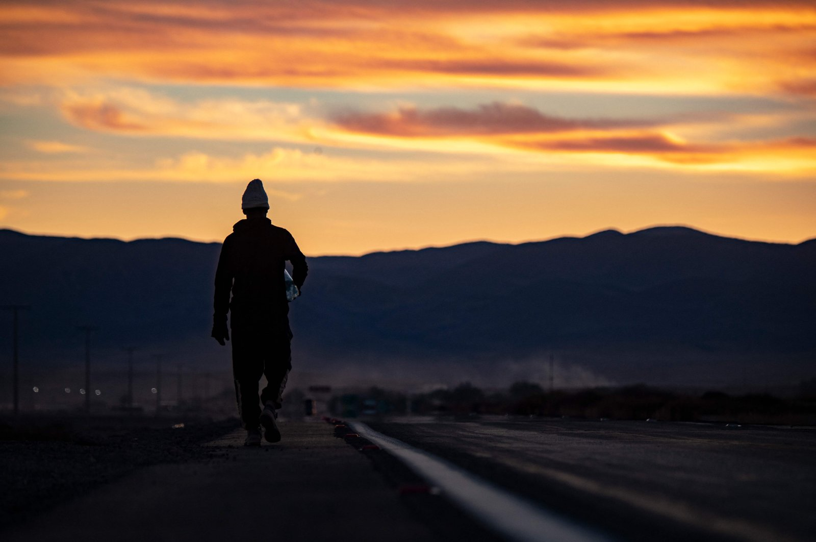A Venezuelan migrant walks along the road linking the border town of Colchane with Iquique, Chile, on Sept. 23, 2021. (AFP Photo)