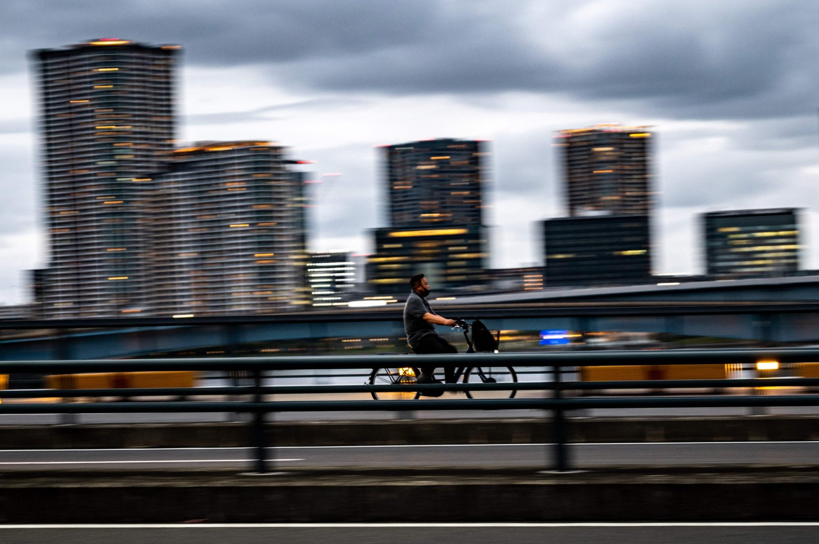 A man rides a bicycle on a footbridge near Tokyo's Toyosu district on October 6, 2021. (AFP Photo)