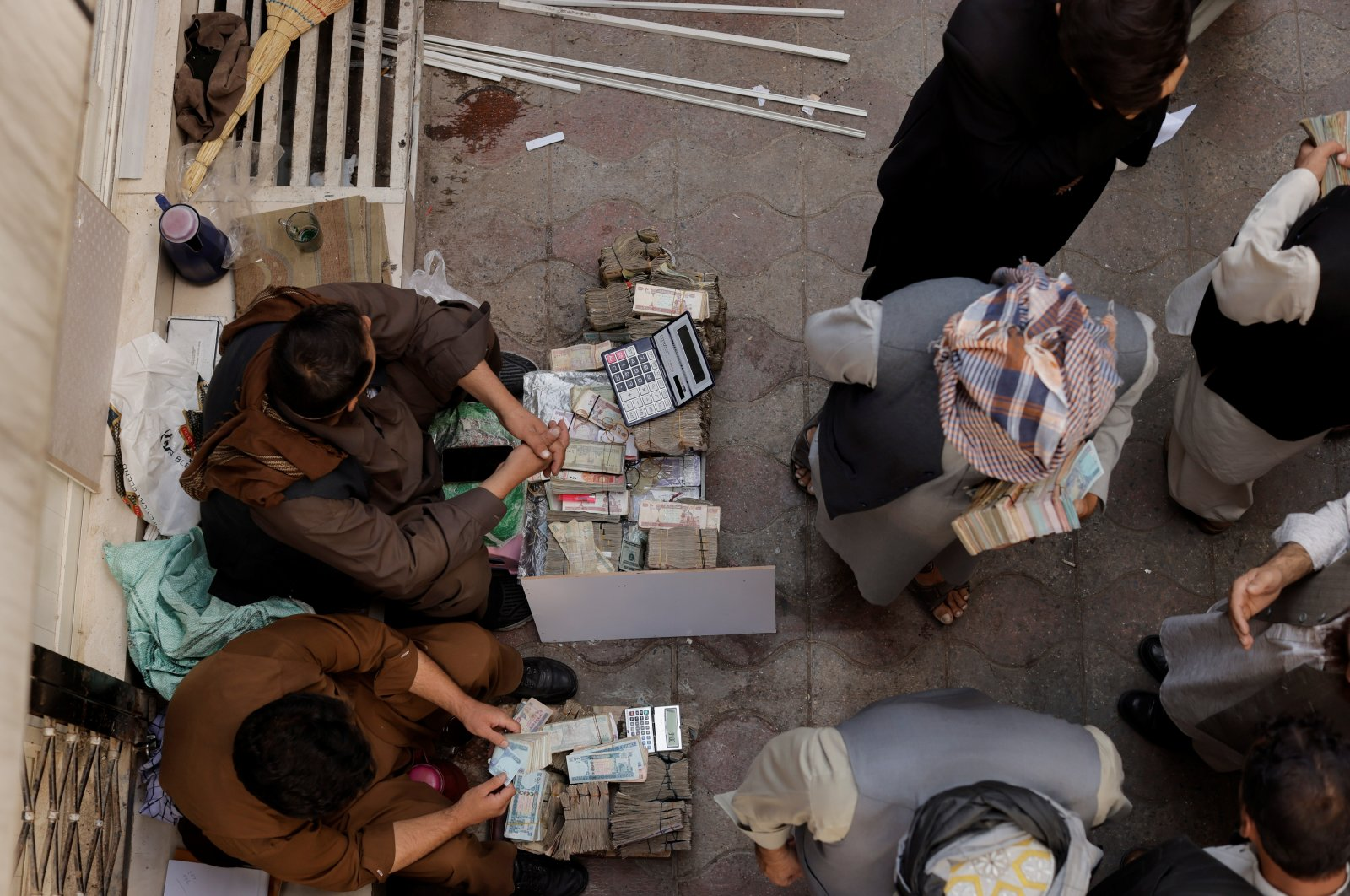Afghan men sit next to stacks of banknotes as people exchange money at a currency exchange market in Kabul, Afghanistan, Oct. 7, 2021. (REUTERS Photo)