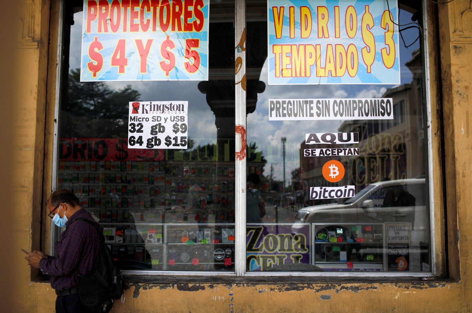 """A man stands by a sign that reads, """"Bitcoin accepted here,"""" outside a store in San Salvador, El Salvador, Sept. 24, 2021. (Reuters Photo)"""