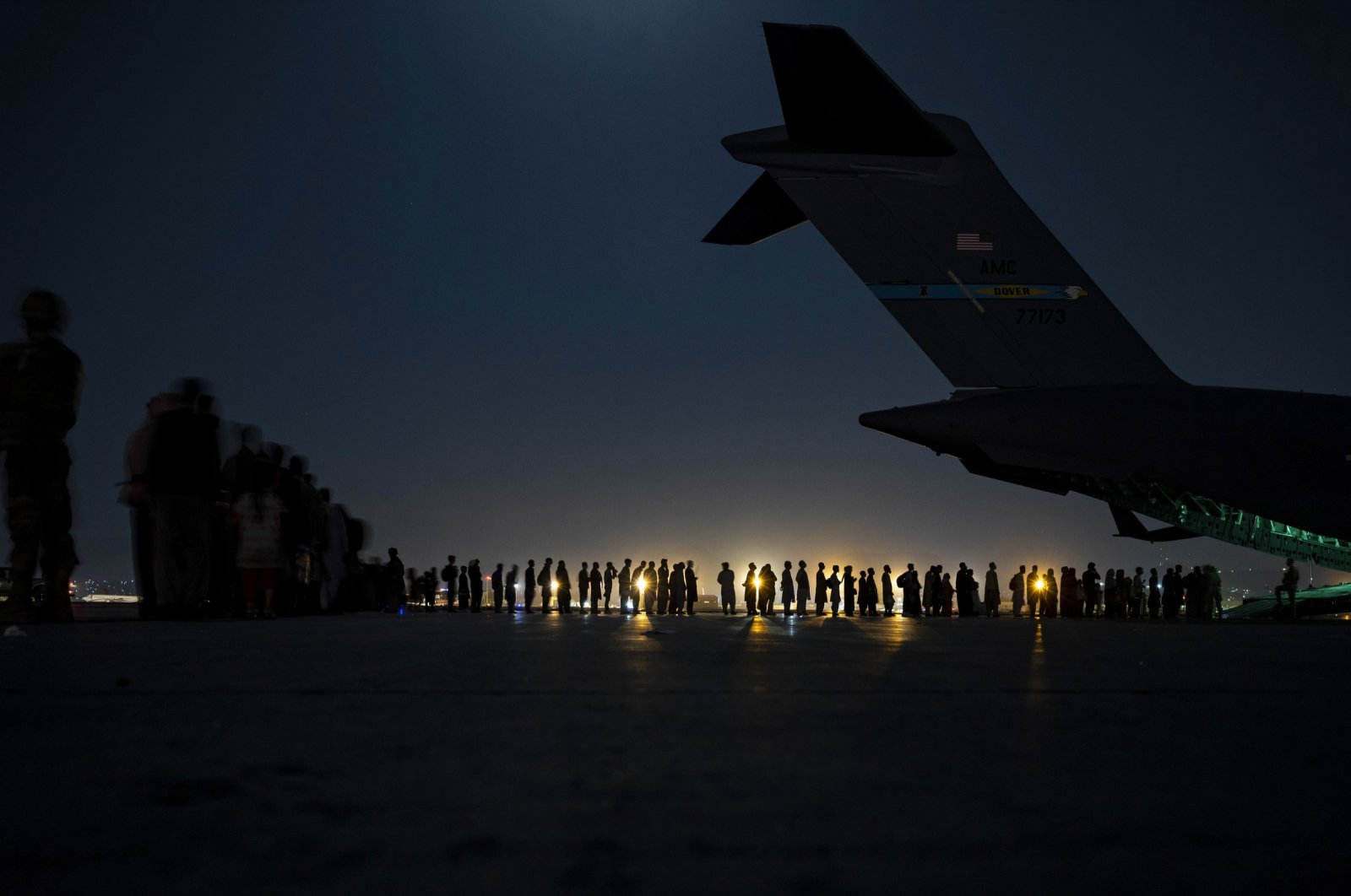 In this image provided by the U.S. Air Force, the U.S. Air Force aircrew, assigned to the 816th Expeditionary Airlift Squadron, prepare to load qualified evacuees aboard a U.S. Air Force C-17 Globemaster III aircraft in support of the Afghanistan evacuation at Hamid Karzai International Airport, Kabul, Afghanistan. (AP Photo)