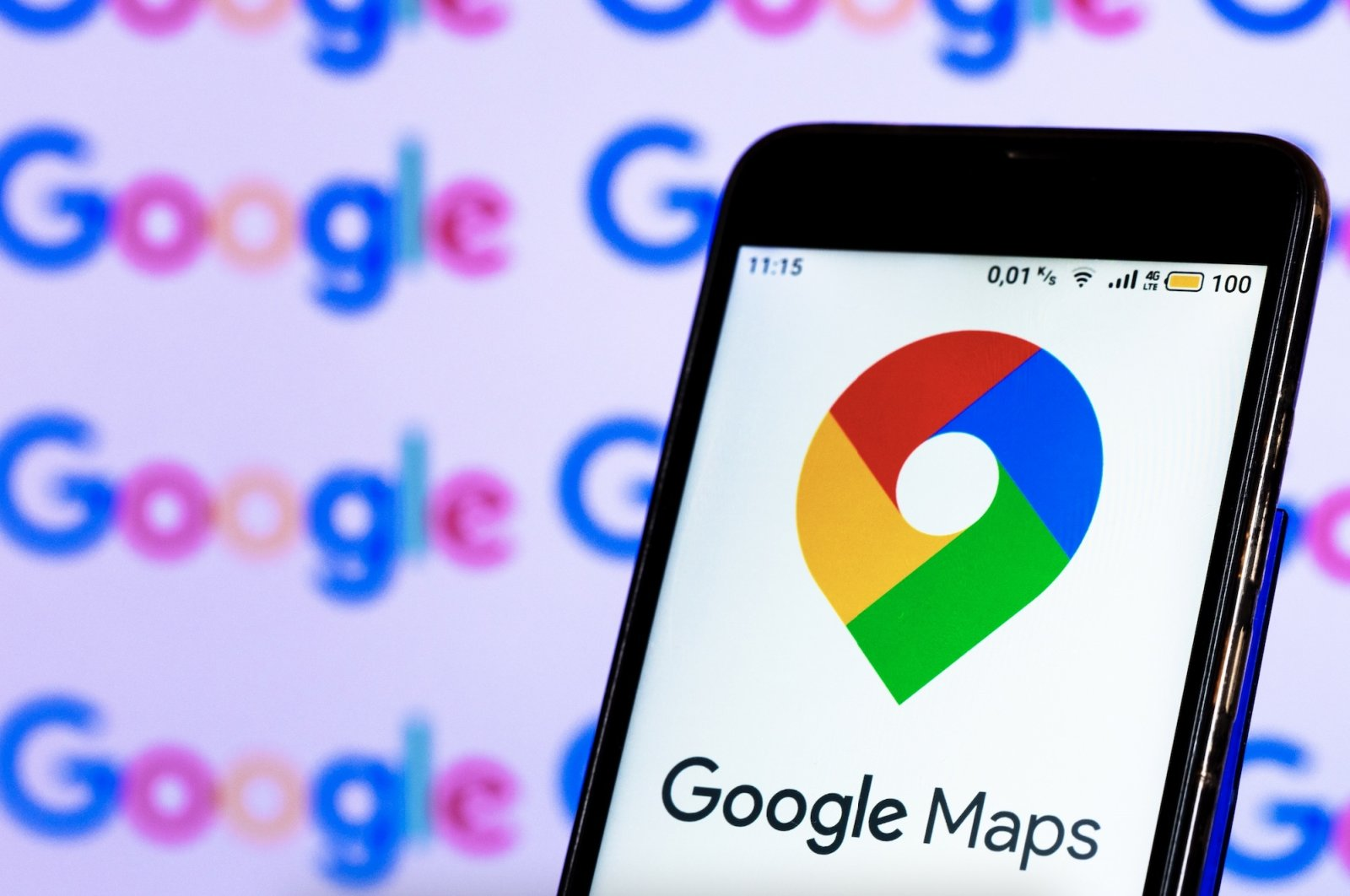 In this photo illustration, a Google Maps logo is seen displayed on a smartphone screen in front of a computer screen. (Reuters Photo)