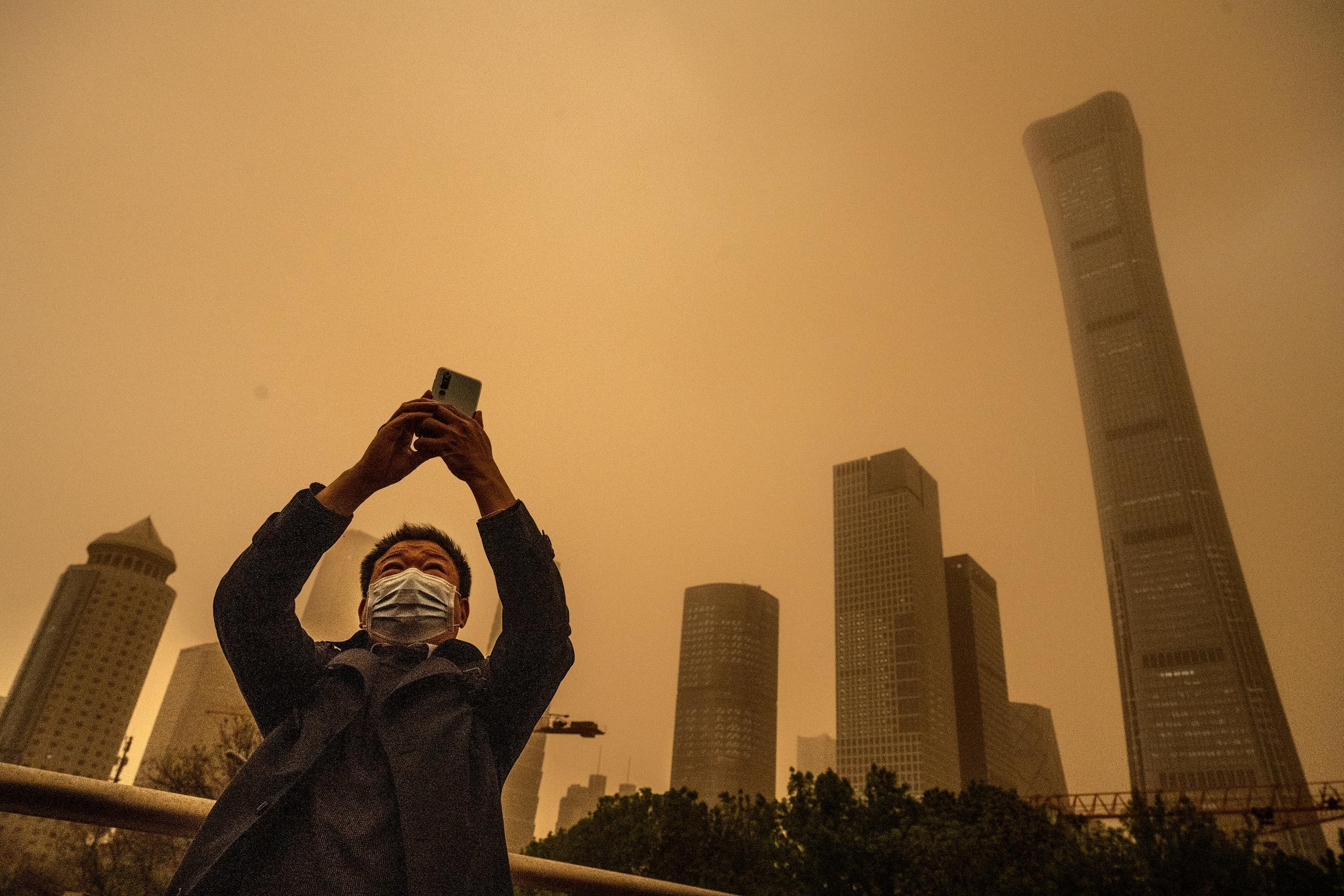 A man wears a protective mask as he takes photos during a seasonal sandstorm, Beijing, China, April 15, 2021. (Photo by Getty Images)