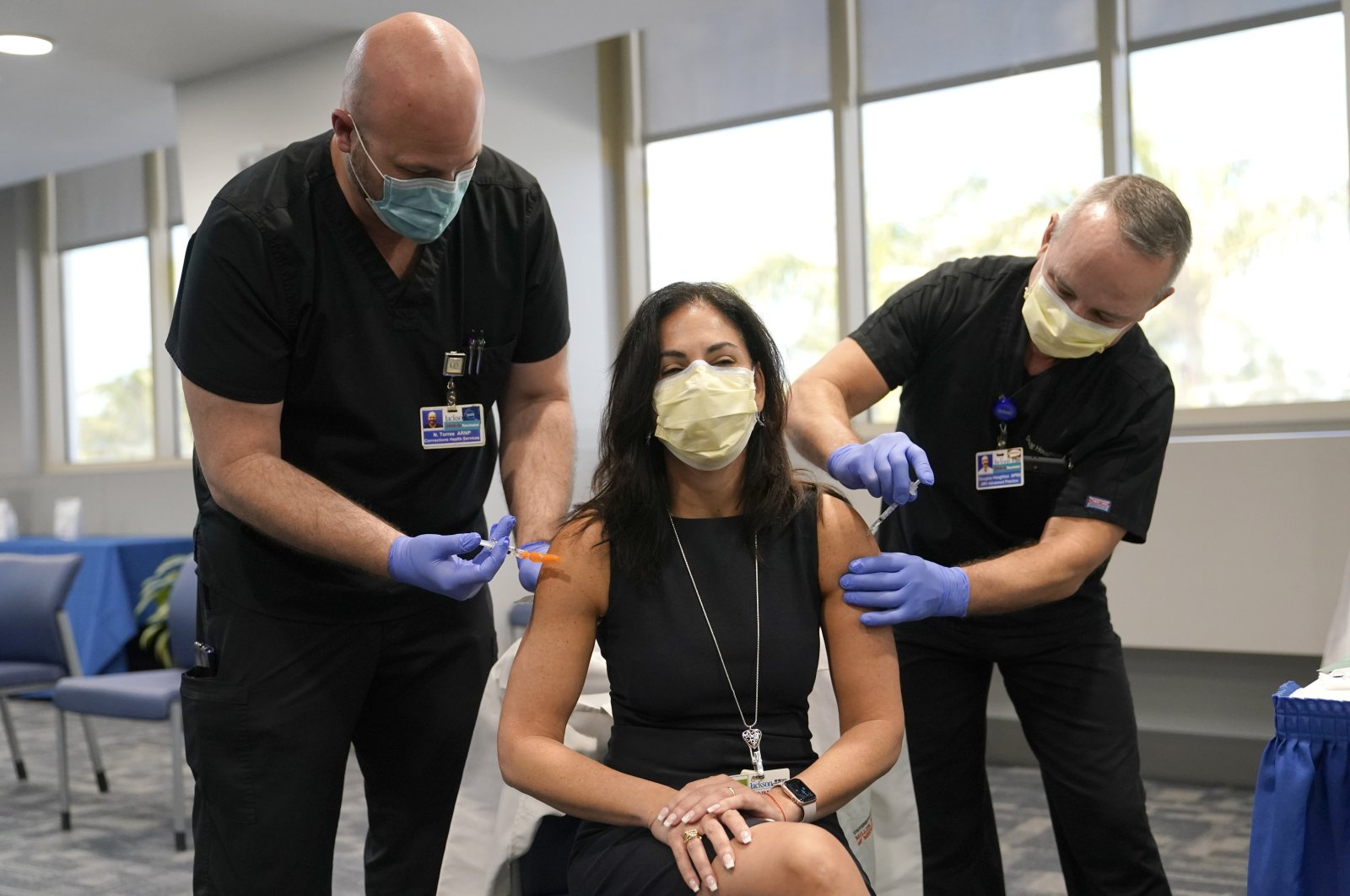 Dr. Lilian Abbo (C), receives a flu vaccine (L), and a Pfizer COVID-19 booster shot (R), at Jackson Memorial Hospital, in Miami, U.S., Oct. 5, 2021. (AP Photo)