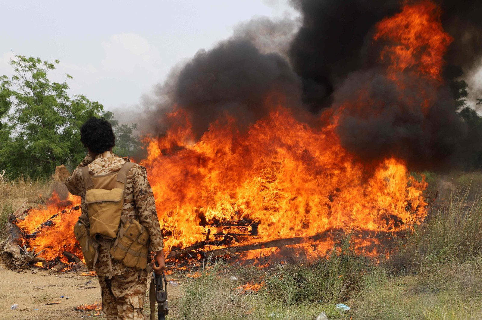 Security forces of the Saudi-backed and internationally recognized Yemeni government incinerate packages of what is reportedly believed to be narcotics seized from across various areas, in Yemen's northern Hajjah province near the border with Saudi Arabia on Oct. 5, 2021. (AFP Photo)