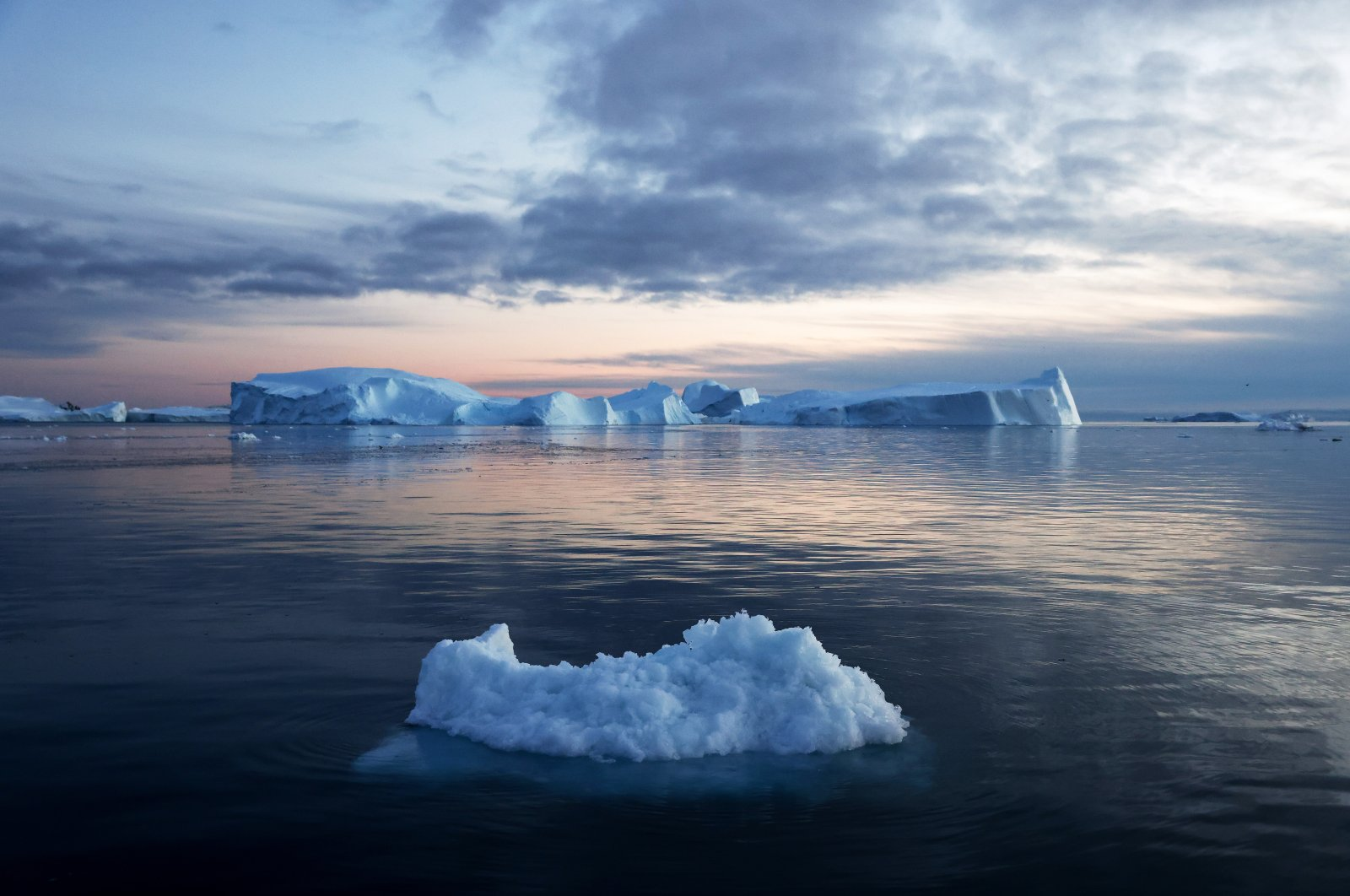 Icebergs that calved from the Sermeq Kujalleq glacier (background) float in the Ilulissat Icefjord, Ilulissat, Greenland, Sept. 5, 2021. (Photo by Getty Images)