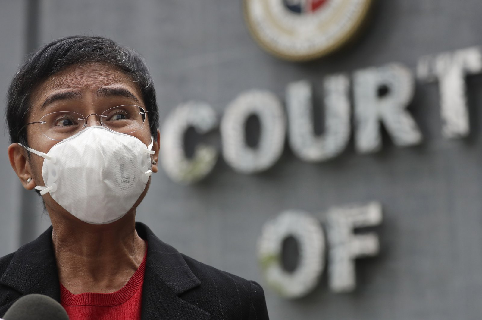 Journalist Maria Ressa, wearing a face mask, talks to reporters outside the Court of Tax Appeals in Manila, Philippines, March 4, 2021. (AP Photo)