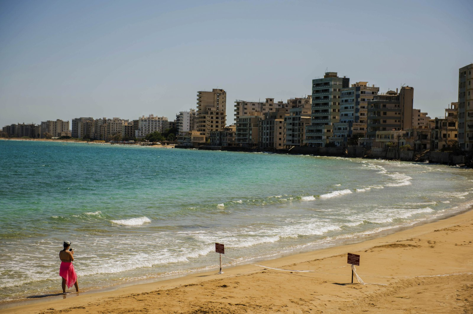 A woman checks her mobile phone as she strolls along an empty stretch of beach in the recently opened ghost suburb of Varosha, Turkish Republic of Northern Cyprus, Sept. 4, 2021. (AP Photo)