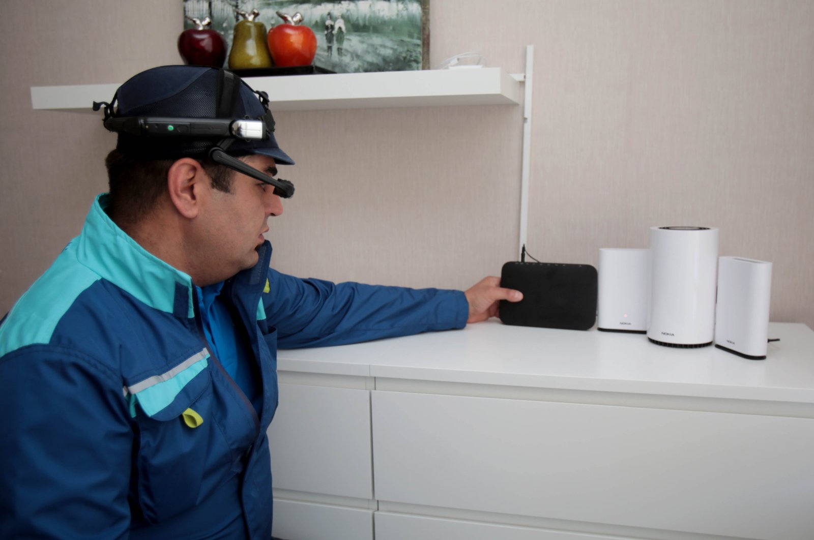 A Türk Telekom field technician equipped with smart glasses checks a modem in this file photo. (Courtesy of Türk Telekom)