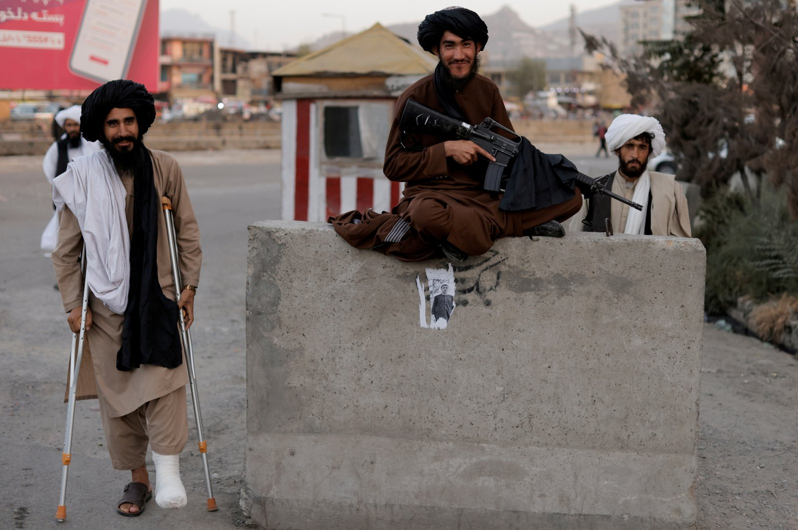 Taliban fighter Mira Jan Himmat, 30, and Rafiullah, 26, from Helmand province smile as they stand guard in a checkpoint in Kabul, Afghanistan, Oct. 5, 2021. (Reuters File Photo)