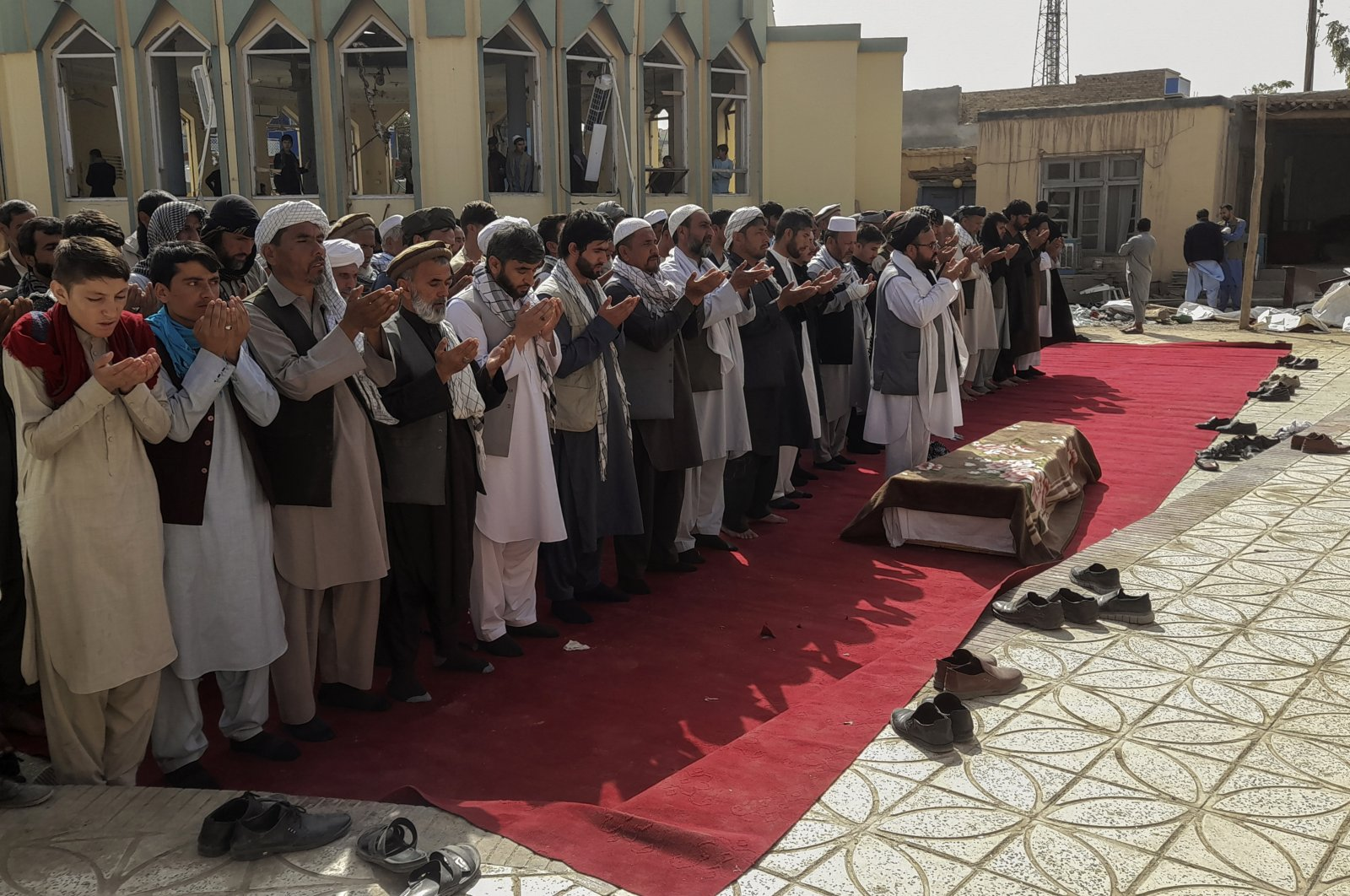 Relatives and residents pray during a funeral ceremony for victims of a suicide attack at the Gozar-e-Sayed Abad Mosque in Kunduz, northern Afghanistan, Oct. 9, 2021. (AP Photo)