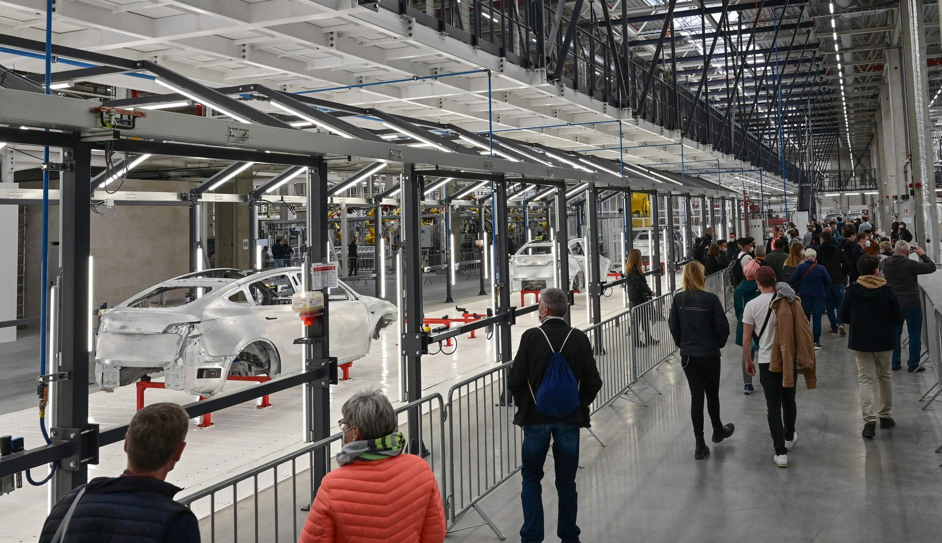 Visitors walk through a factory building during the opening of the Tesla Gigafactory in Gruenheide, east of Berlin, Germany, Oct. 9, 2021. (AFP Photo)