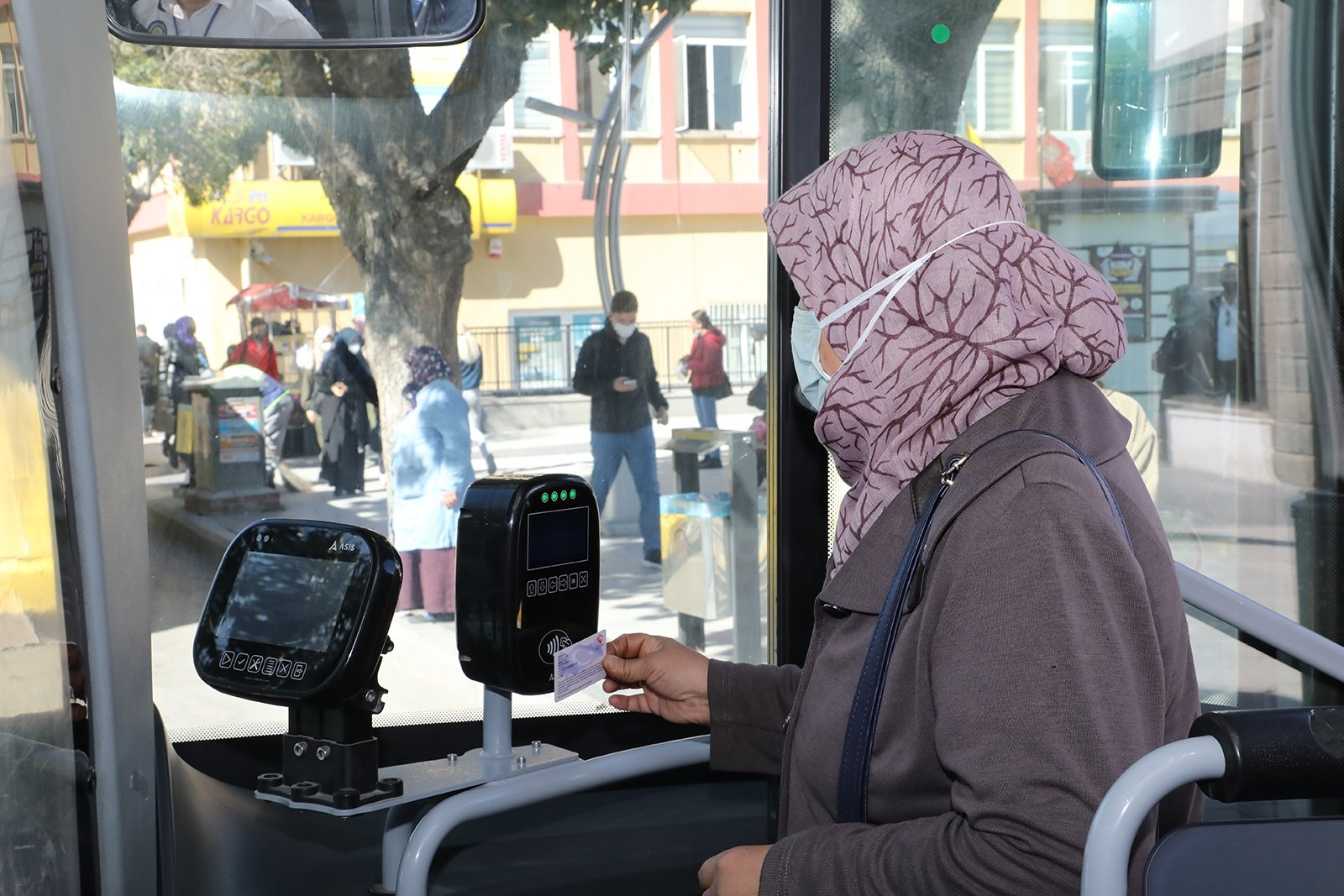 A passenger scans her electronic pass in a bus, in Afyon, western Turkey, Oct. 5, 2021. (AA Photo)