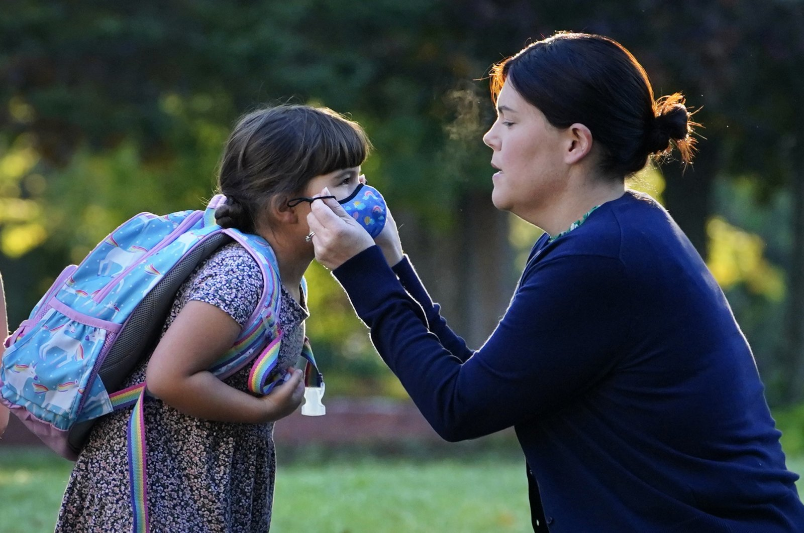 Sarah Staffiere adjusts a face covering on her daughter, Natalie, before school, in Waterville, Maine, U.S., Oct. 7, 2021. (AP Photo)
