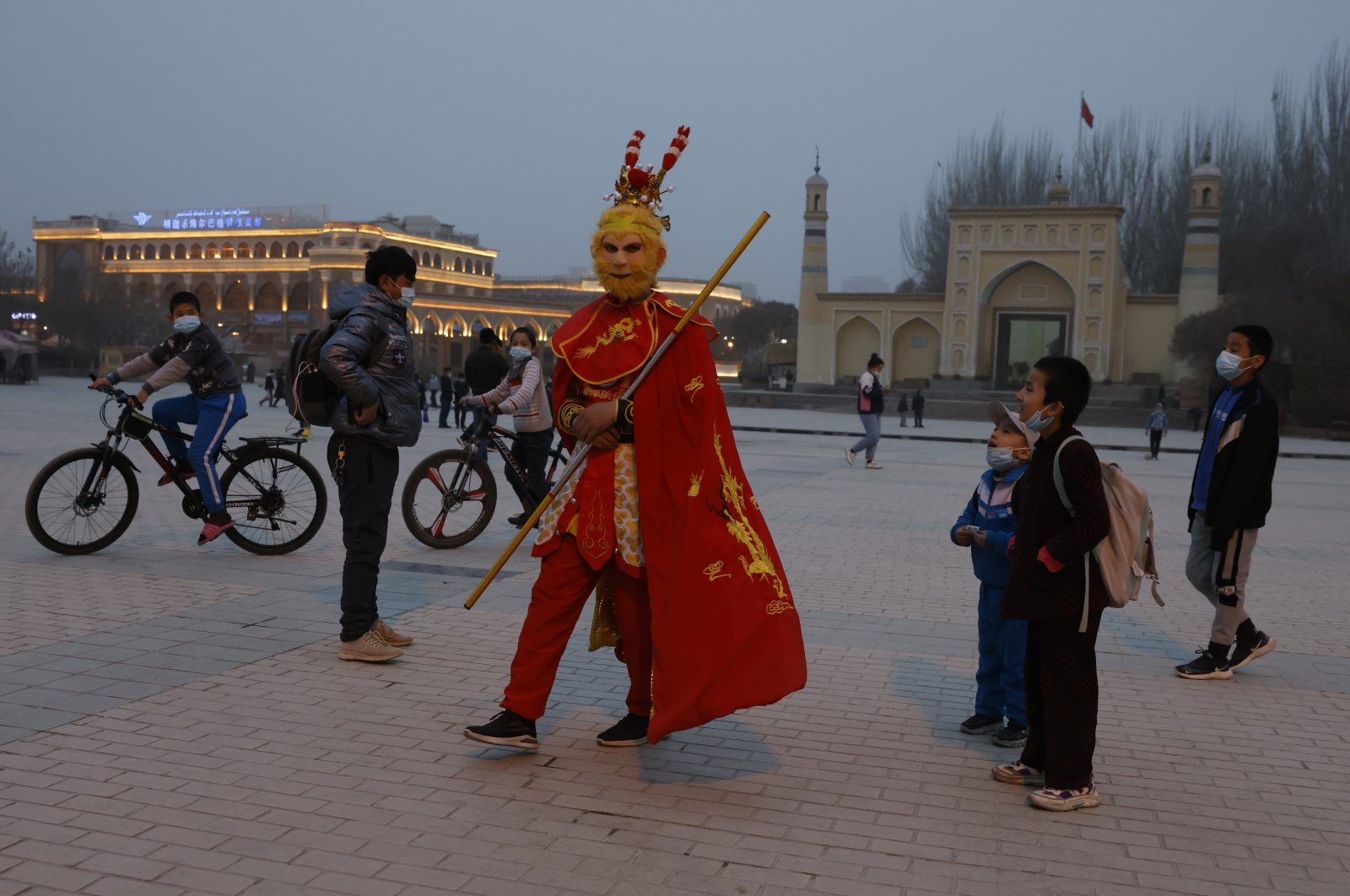 A performer dressed as the monkey god from a Chinese fable walks near a mosque as Uyghur children gaze upon him in Kashgar, Xinjiang Uyghur Autonomous Region, China, March 19, 2021. (AP Photo)