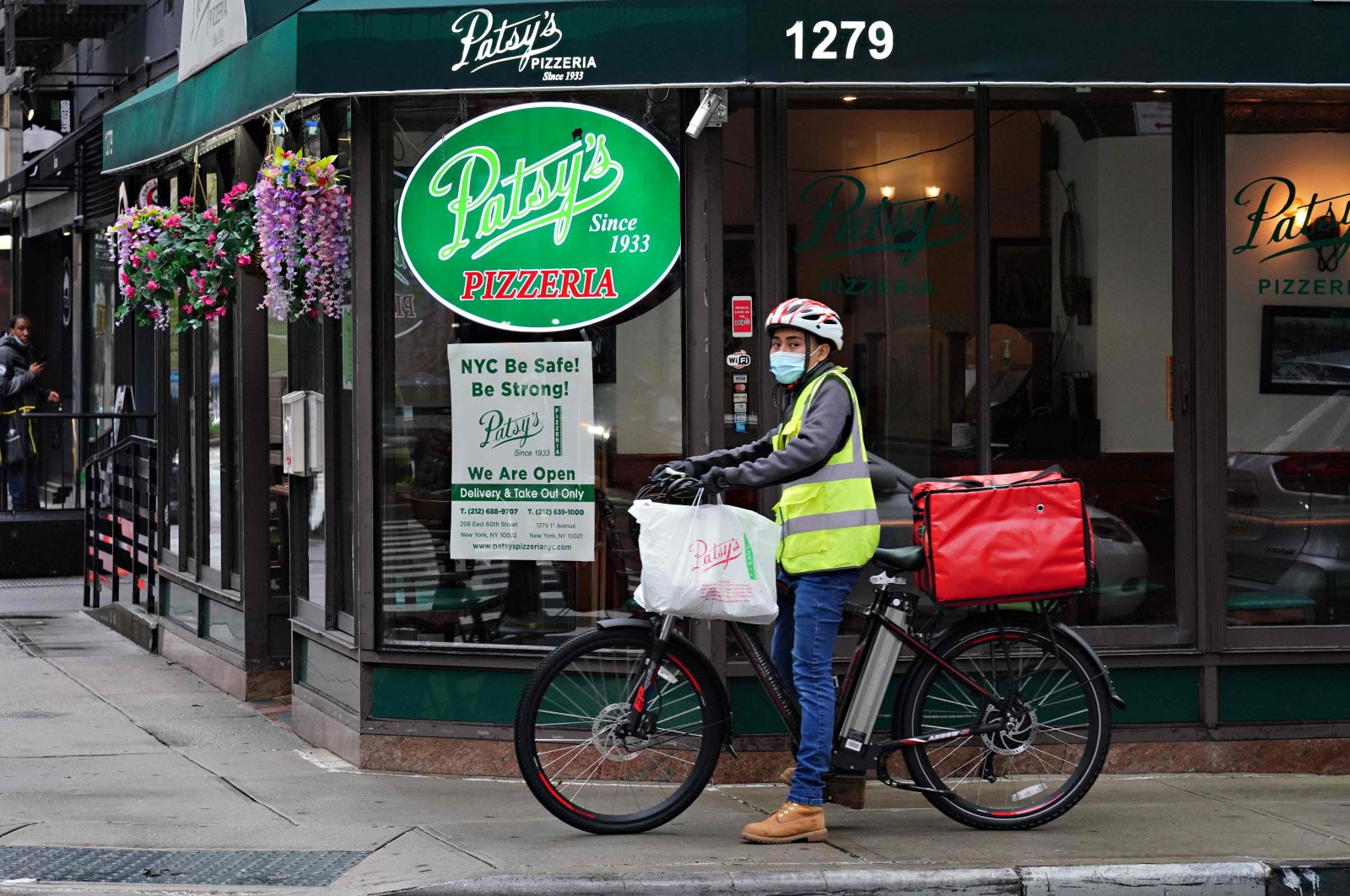 """A restaurant delivery worker on his bike stops by a sign in the window of Patsy's Pizzeria which reads """"NYC Be Safe! Be Strong!"""" during the coronavirus pandemic in New York City, U.S., April 23, 2020. (AFP Photo)"""