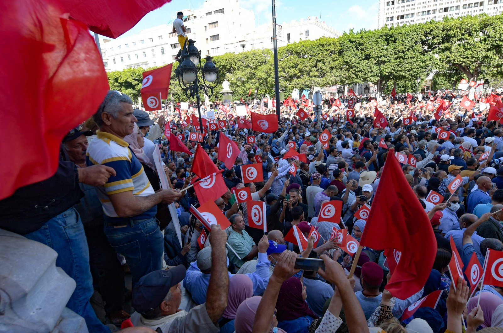 Tunisians raise national flags during a rally against their president along the Habib Bourguiba avenue in the capital Tunis, Oct. 10, 2021. (AFP Photo)
