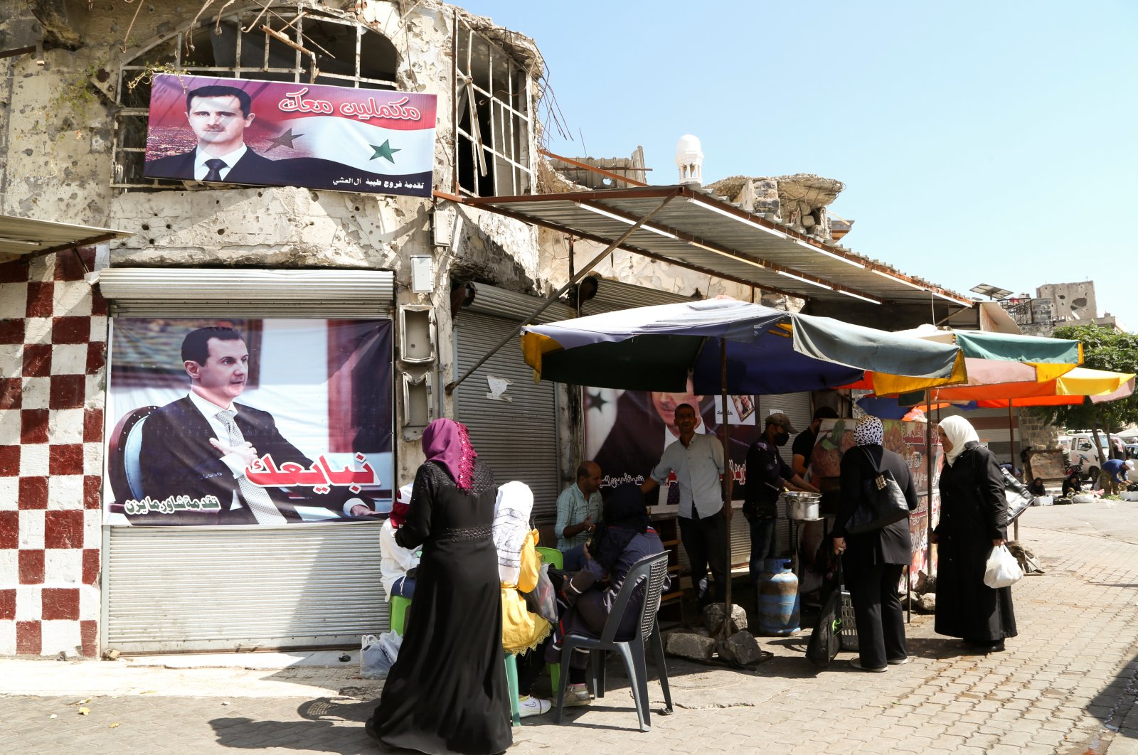 People stand near posters depicting Bashar Assad in Homs, Syria, Oct. 3, 2021. (REUTERS)