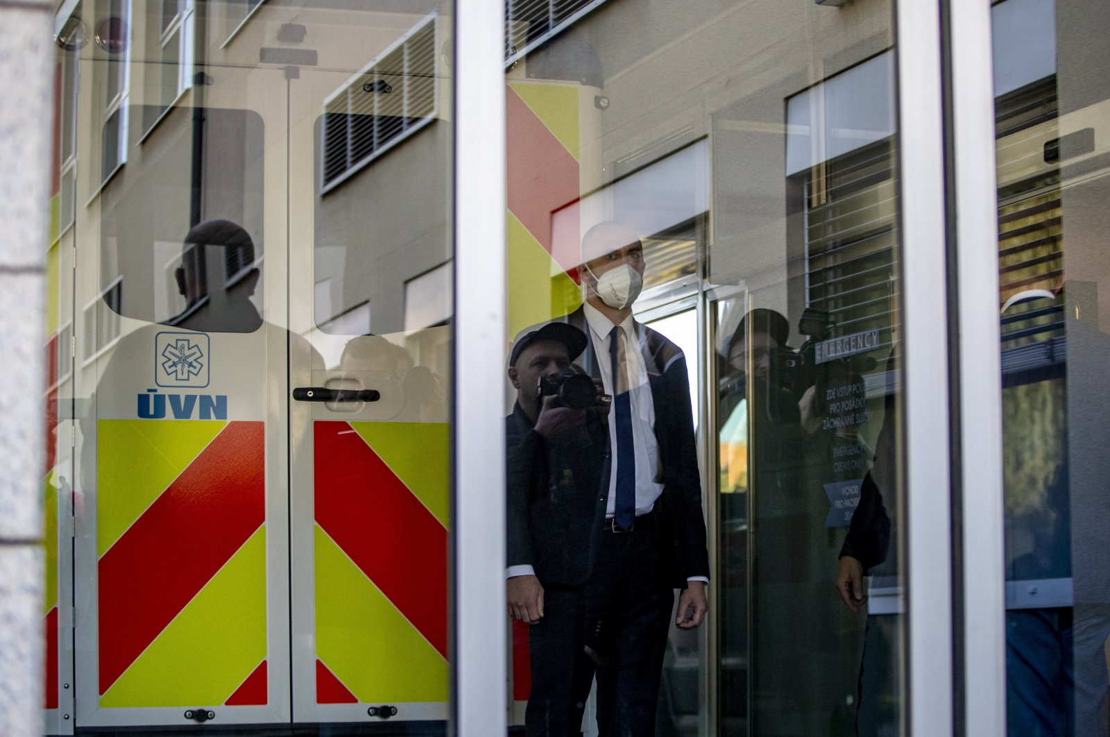 Media members are reflected in a glass door as security guards an ambulance carrying Czech President Milos Zeman arriving at the Central Military Hospital in Prague, Czech Republic, Oct. 10, 2021. (EPA Photo)