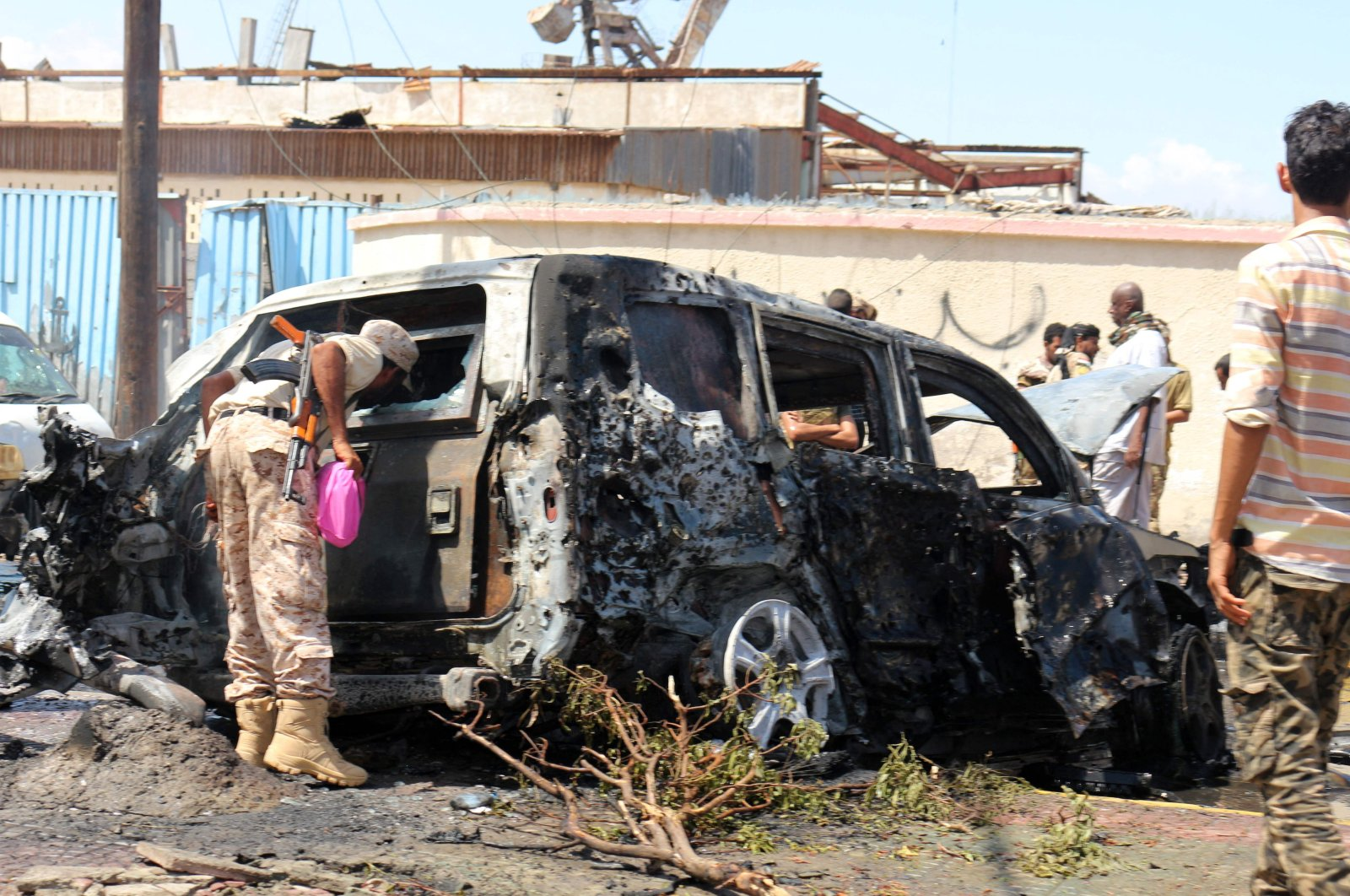Yemeni security forces and rescue teams gather around the carcass of a burnt car following an explosion that hit Yemen's southern port city of Aden, Oct. 10, 2021. (AFP Photo)