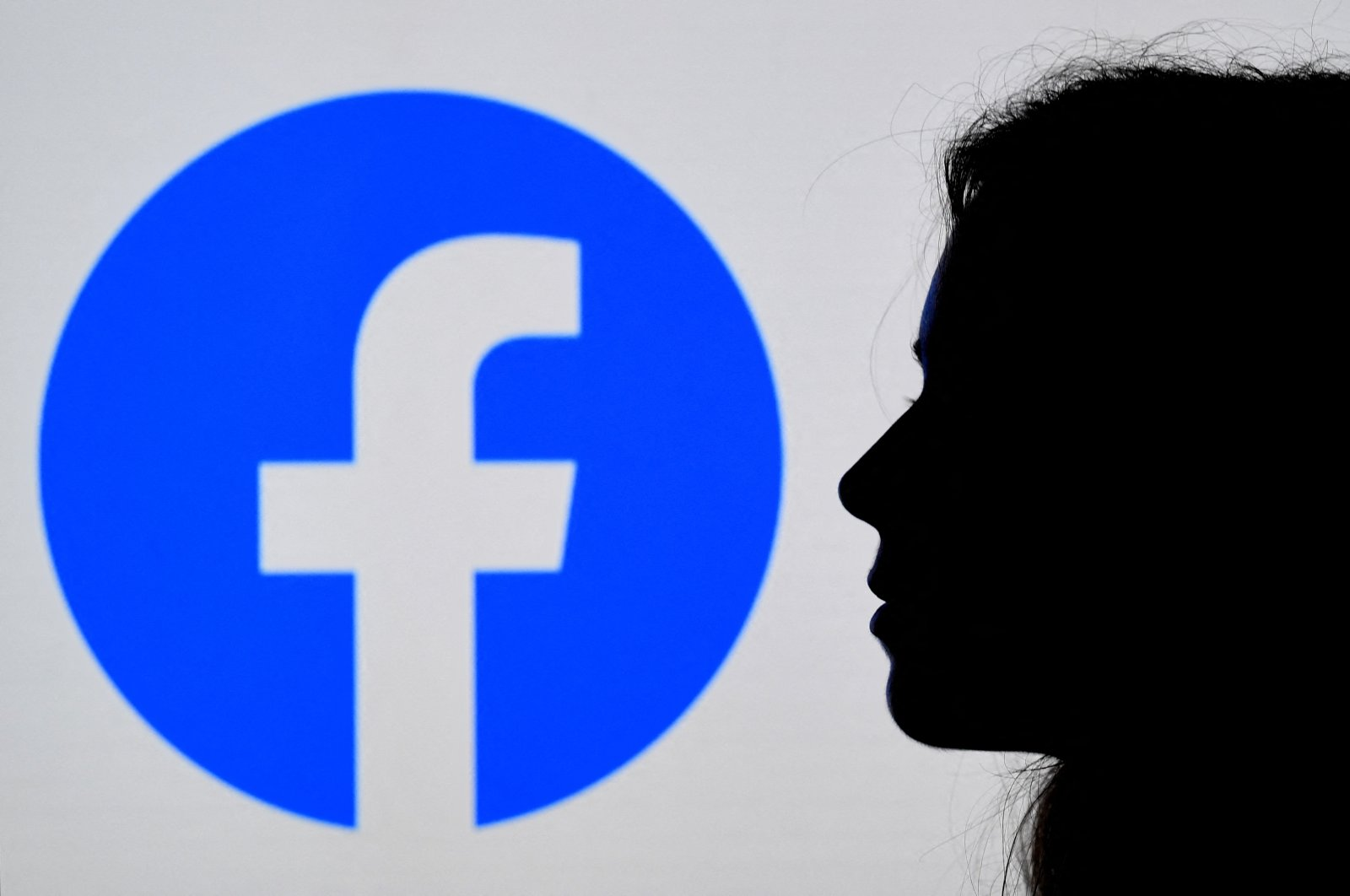 In this photo illustration, a person looks at a smartphone with a Facebook App logo displayed on the background, in Arlington, Virginia, U.S., Aug. 17, 2021. (AFP Photo)