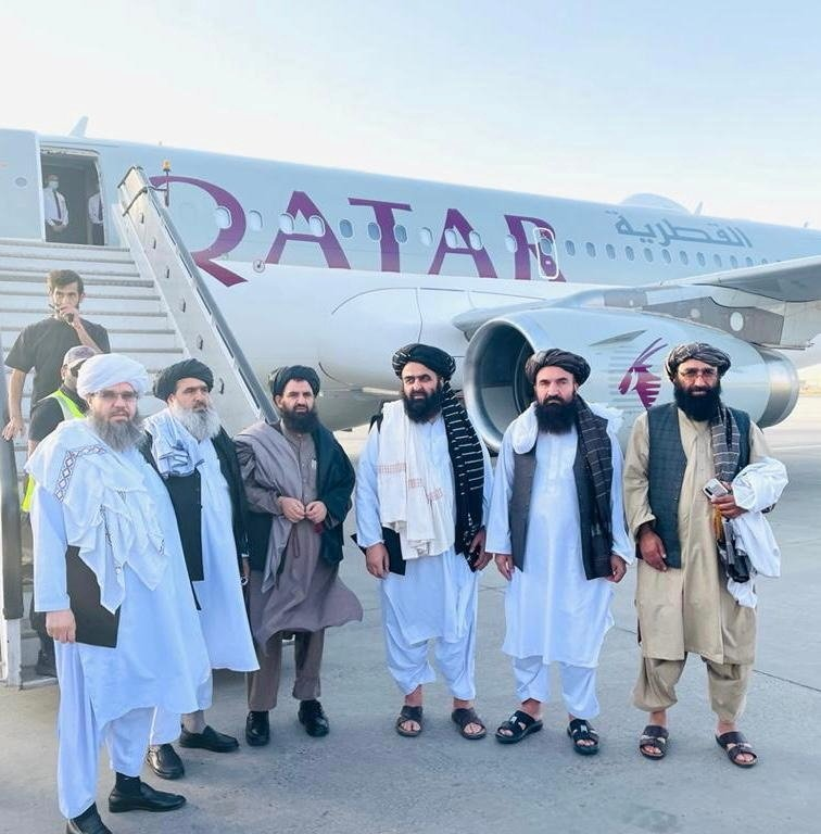 Taliban delegates stand in front of a Qatar Airways plane at an unidentified location in Afghanistan, in this handout photo uploaded to social media on Oct. 8, 2021. (Reuters Photo)