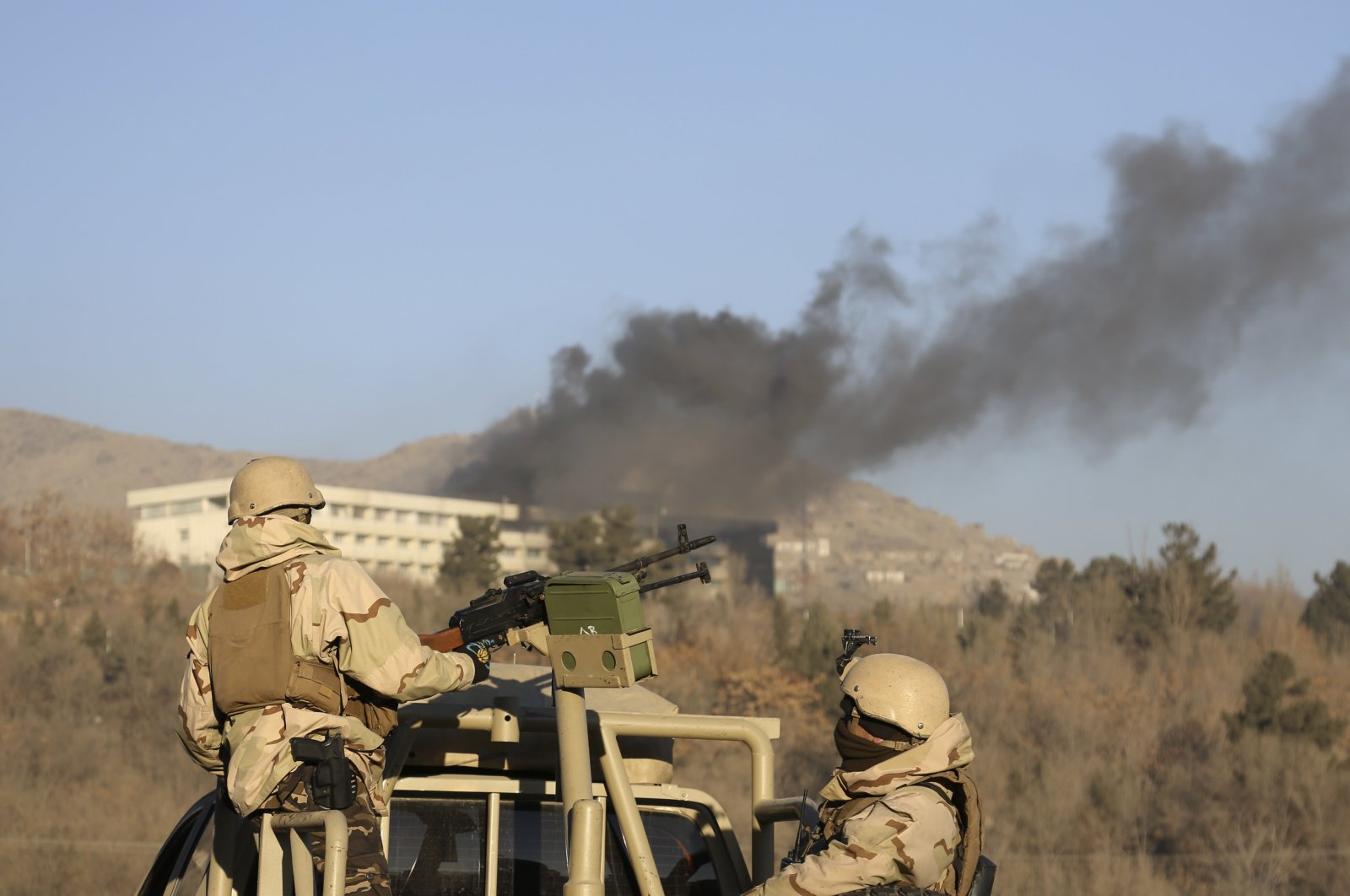 Afghan security personnel stand guard as smoke rises from the Intercontinental Hotel after an attack in Kabul, Afghanistan, Jan. 21, 2018. (AP Photo)