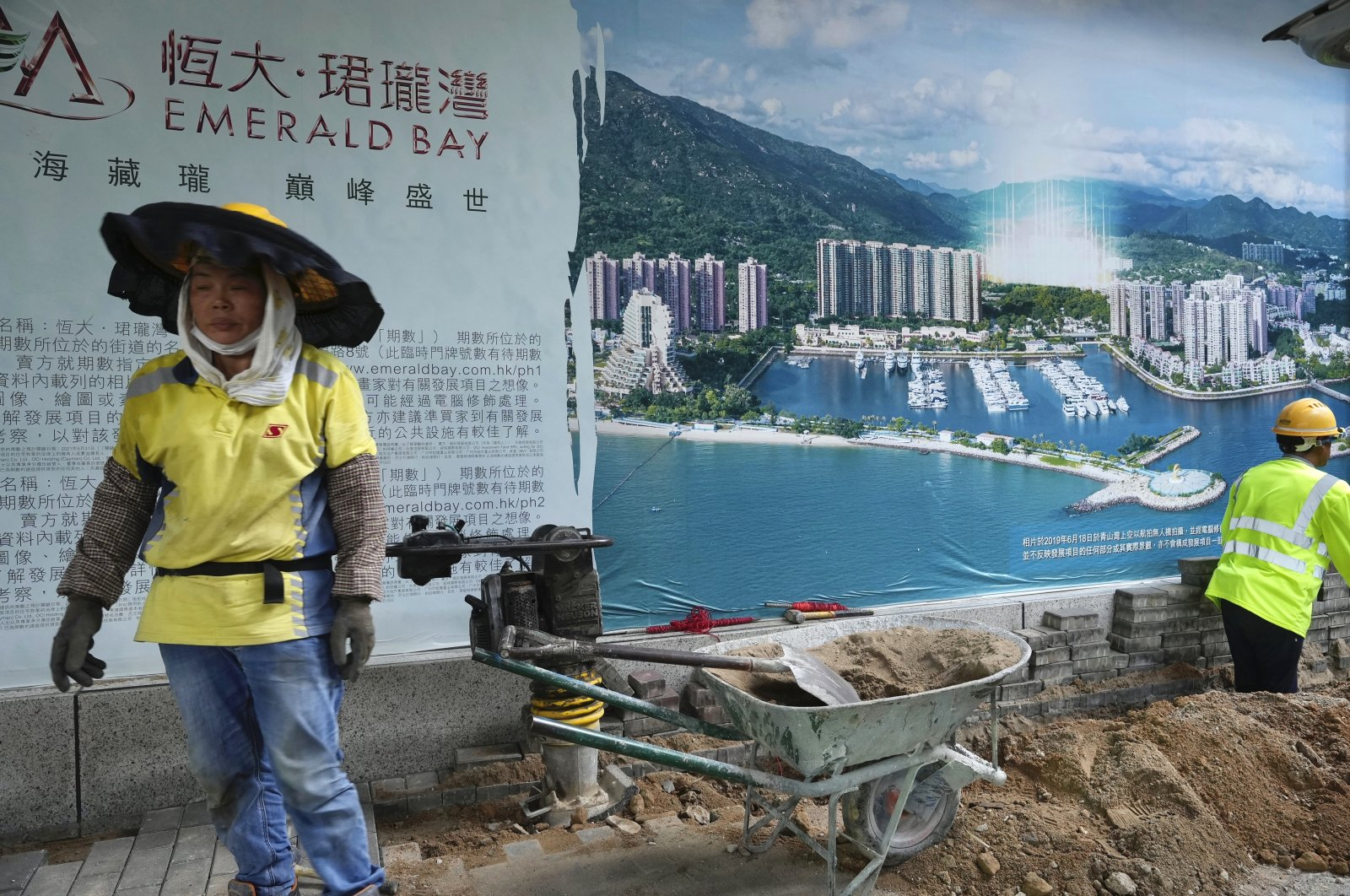 A worker walks past an advertisement photo of a China Evergrande Group property project outside its headquarters in Hong Kong, China, Oct. 4, 2021. (AP Photo)