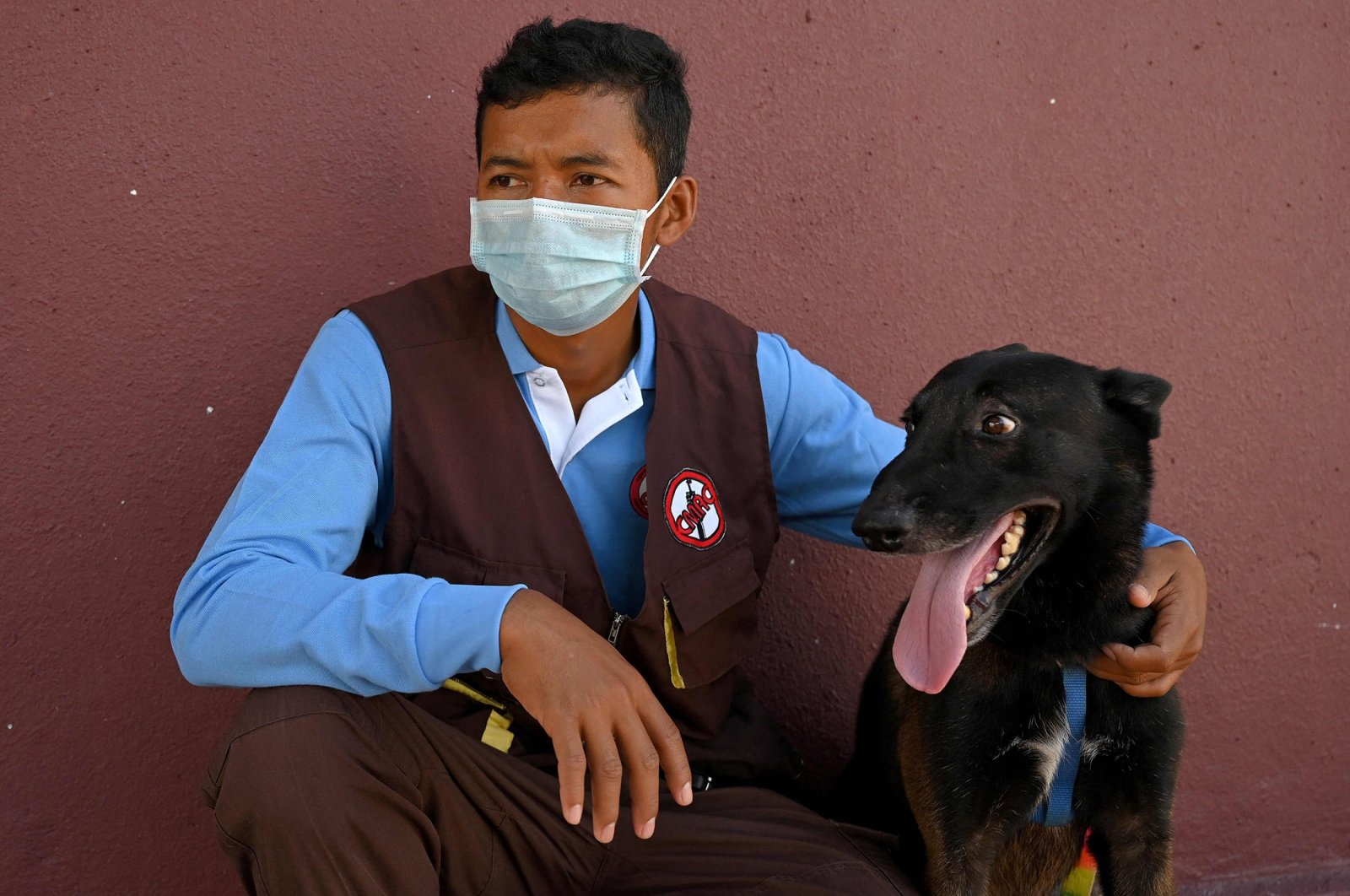 Trainer Khom Sokly sits with a dog trained to detect COVID-19 after a training session at the Cambodian Mine Action Centre (CMAC) in Kampong Chhnang province, Cambodia, Sept. 27, 2021. (AFP Photo)