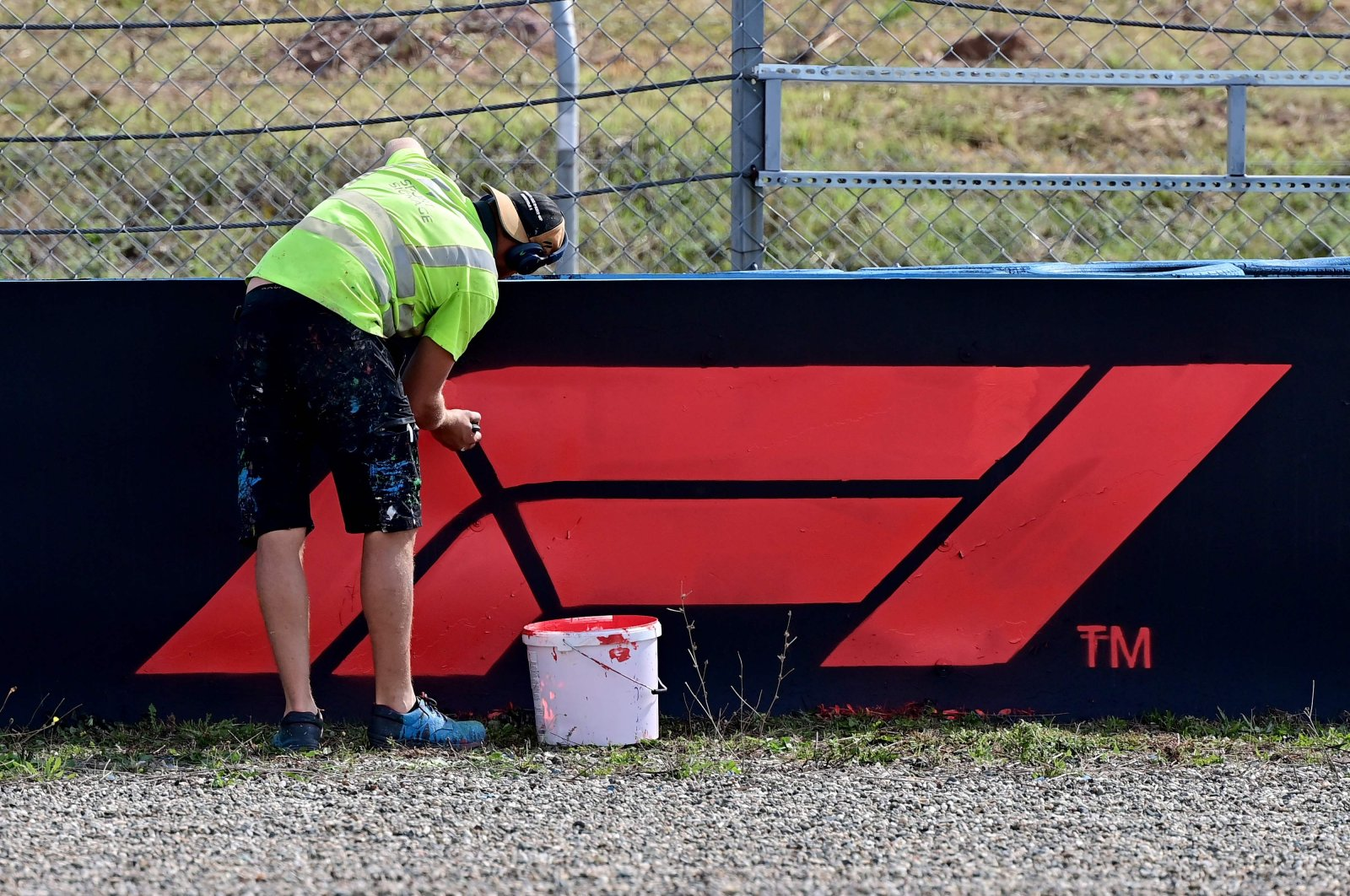 A worker paints the F1 logo on a board on the side of the tracks of Intercity Istanbul Park in Istanbul, Turkey, Oct. 7, 2021. (AFP Photo)