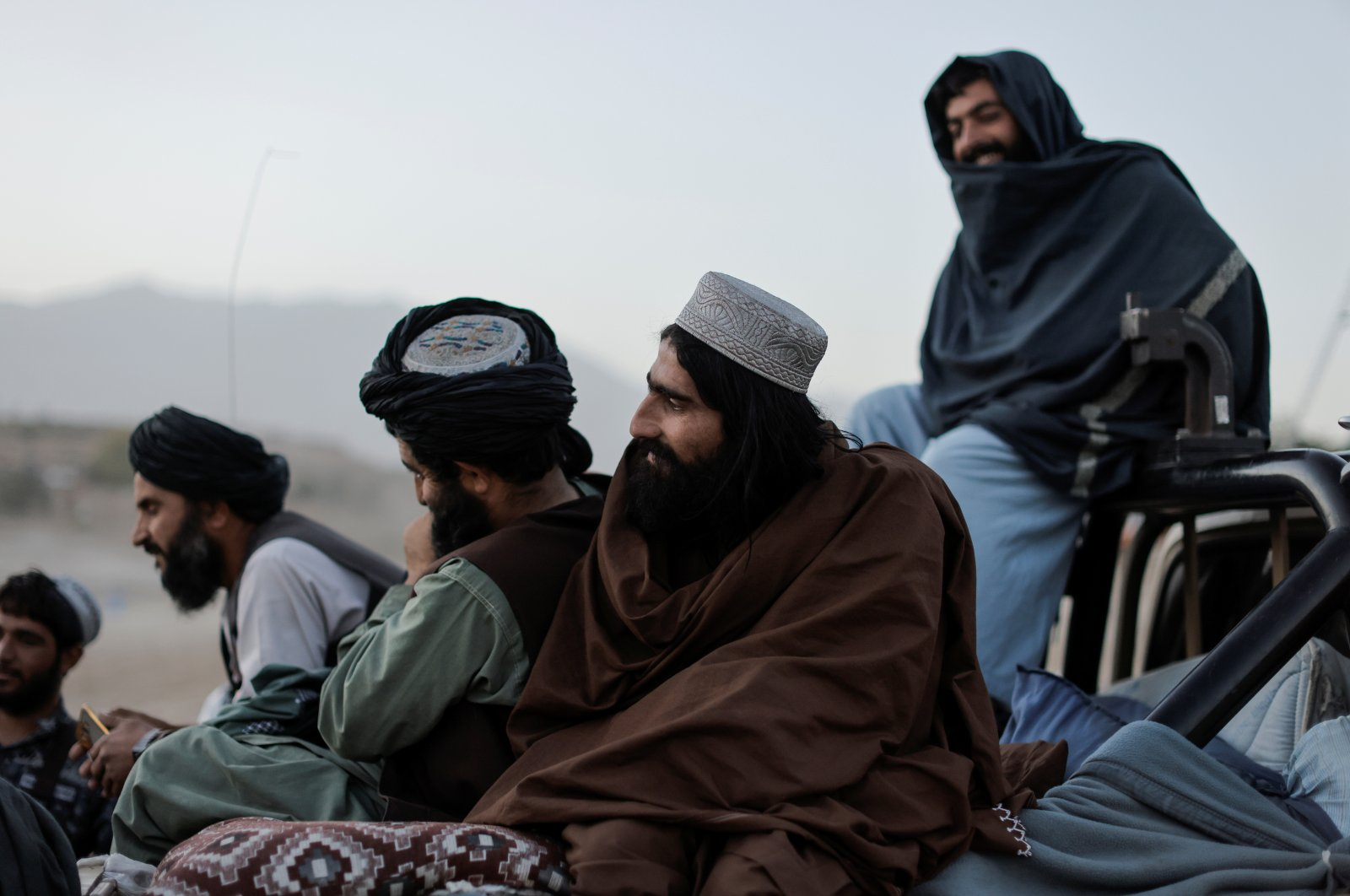 Taliban fighters sit on a vehicle as they take a day off to visit the amusement park at Kabul's Qargha reservoir, at the outskirts of Kabul, Afghanistan October 8, 2021. (Reuters Photo)