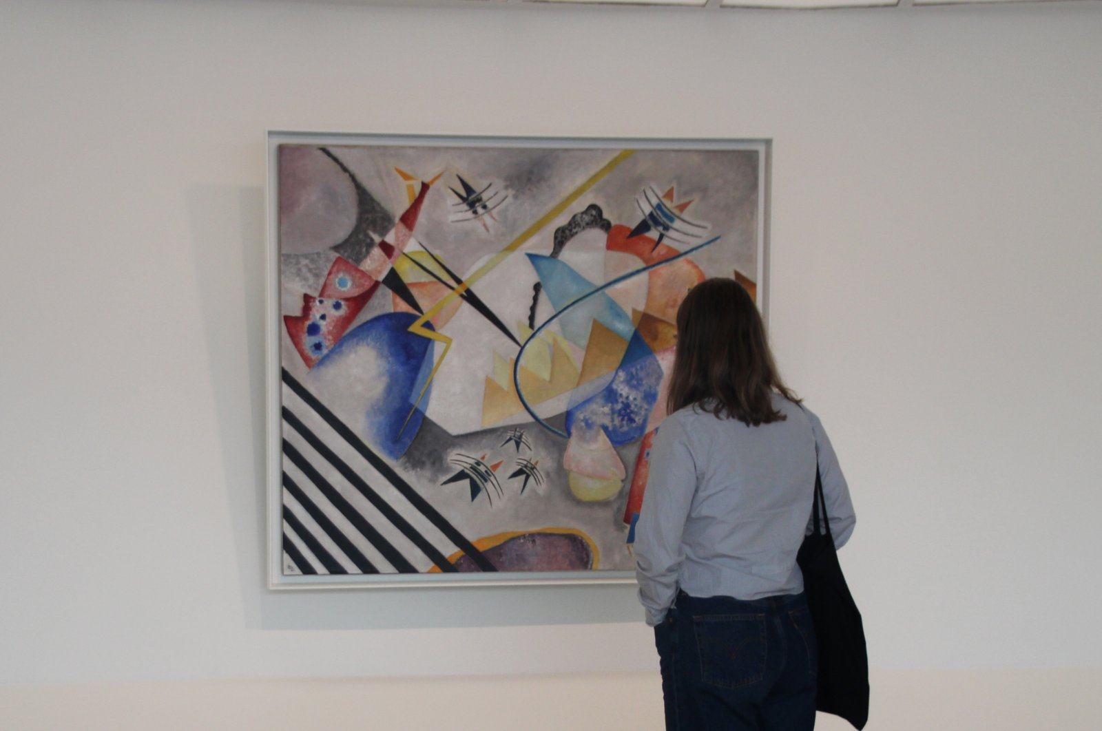 A visitor examines a work by Russian artist Wassily Kandinsky at New York's Guggenheim museum. (DPA Photo)