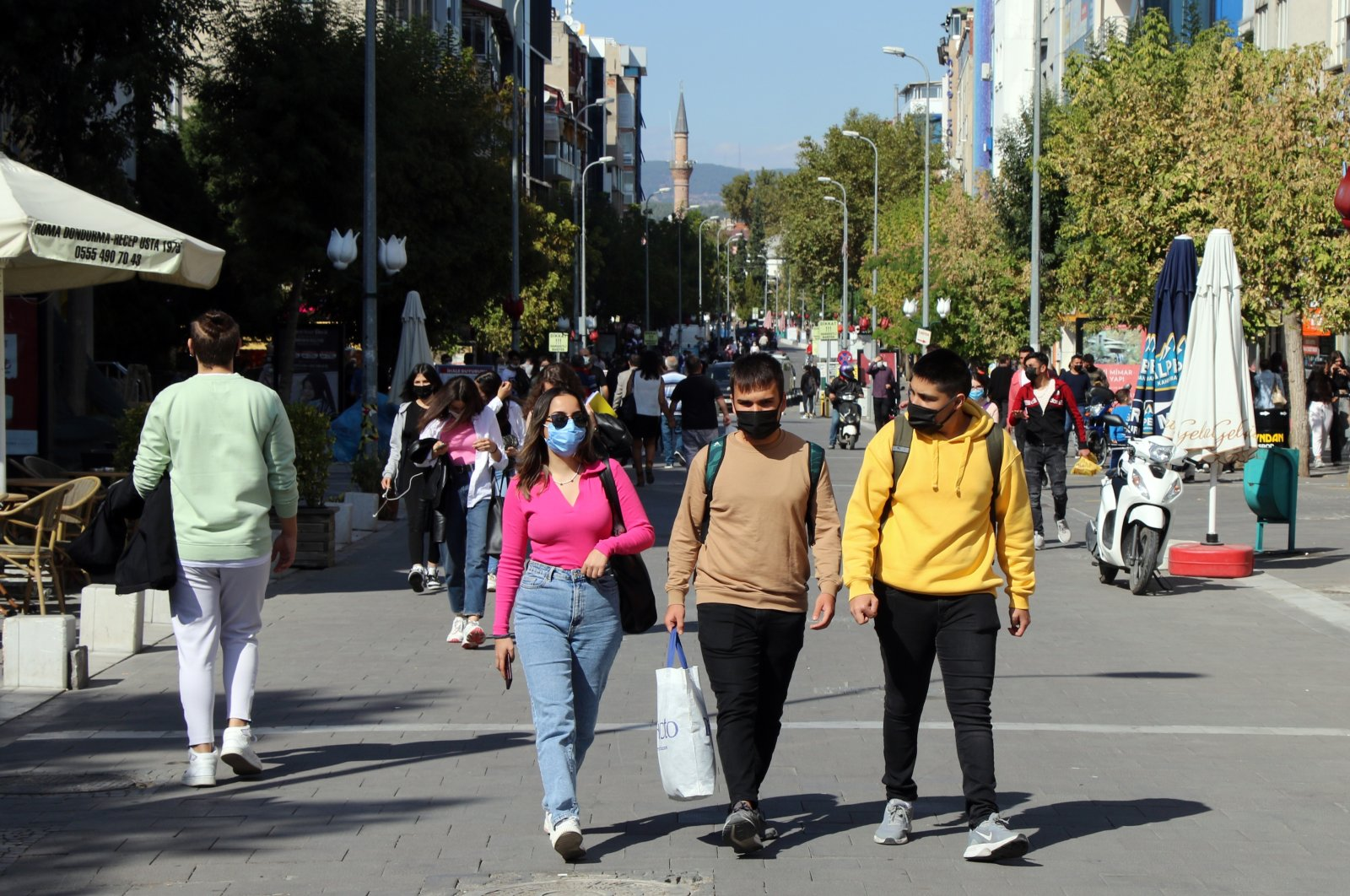 People wearing protective masks against COVID-19 walk on a street in Uşak, western Turkey, Oct. 10, 2021. (AA Photo)
