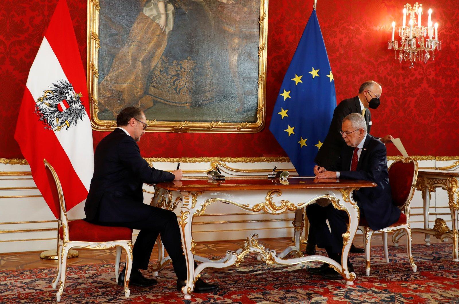 Austria's President Alexander Van der Bellen and new Chancellor of the People's Party (ÖVP) Alexander Schallenberg sign contracts during the swearing-in ceremony in Vienna, Austria, Oct. 11, 2021. (Reuters Photo)