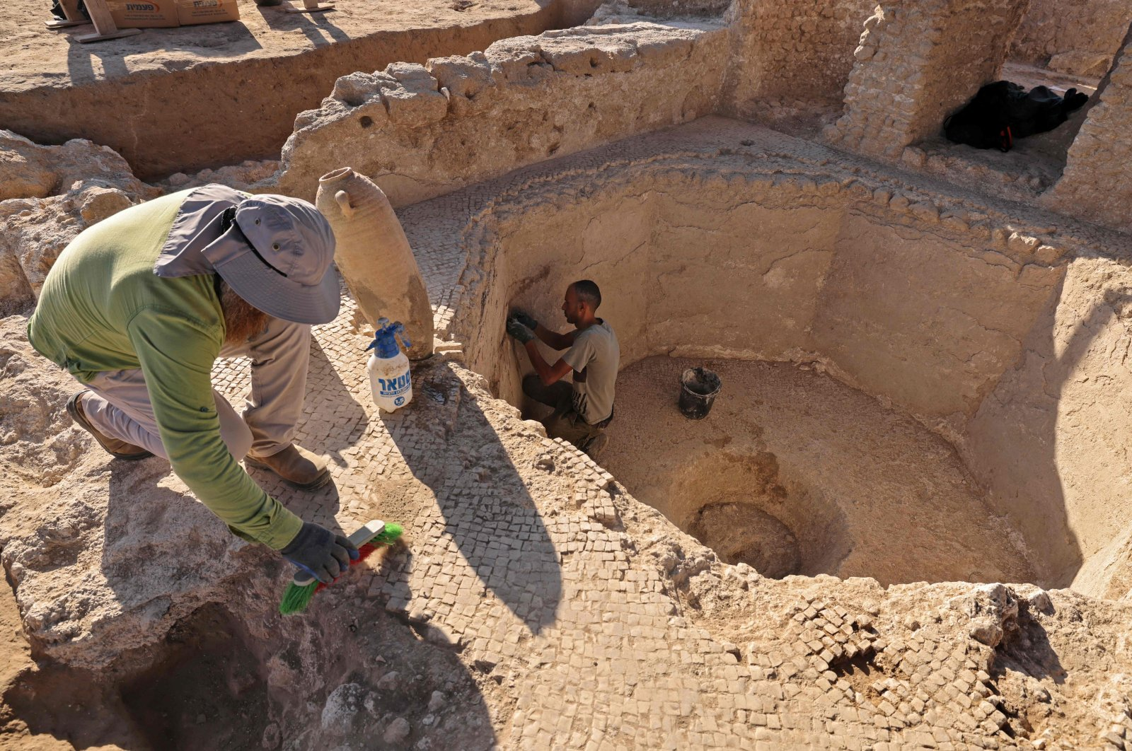 Archaeologists and technicians of the Israel Antiquities Authority excavate inside a collecting vat of a winepress at the Tel Yavne site in central Israel, Oct. 11, 2021. (AFP Photo)