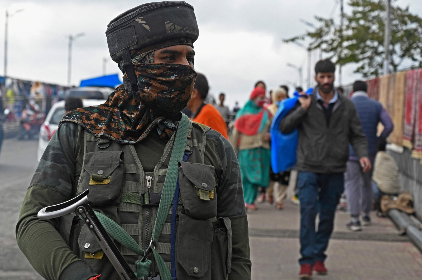 A security personnel stands guard at a market in Srinagar on Oct. 11, 2021, after suspected militants shot dead five soldiers in Indian-administered Kashmir. (AFP)