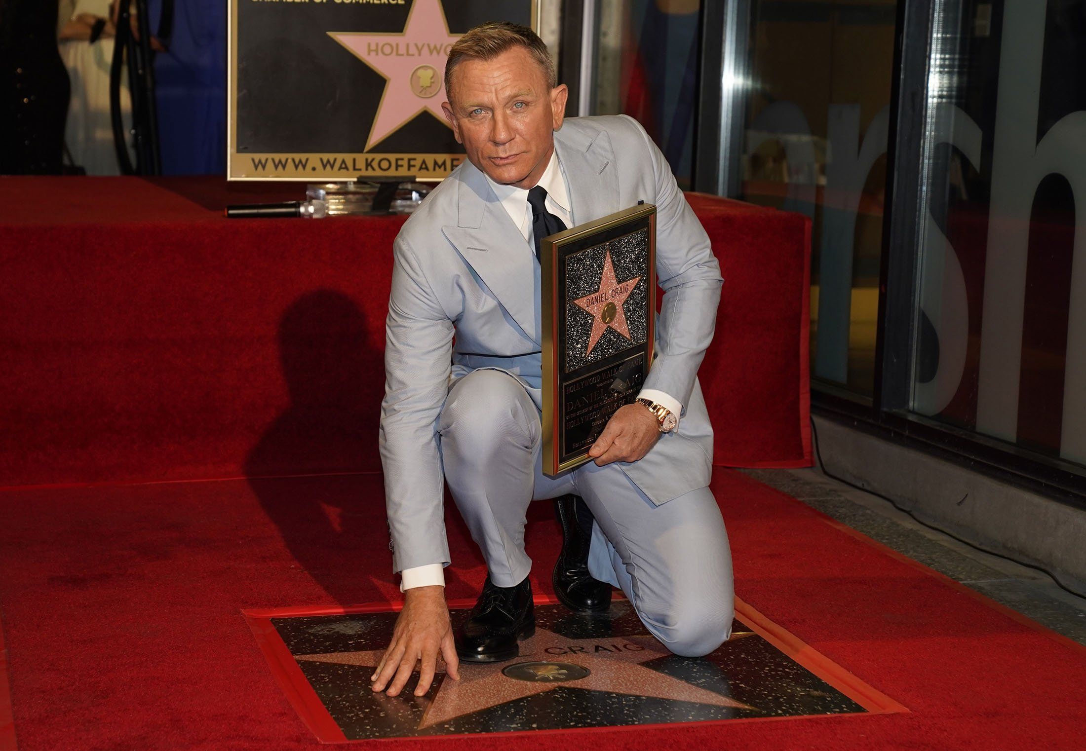 Daniel Craig poses atop his new star on the Hollywood Walk of Fame while holding a replica of the star during a ceremony in his honor in Los Angeles, U.S., Oct. 6, 2021. (AP Photo)